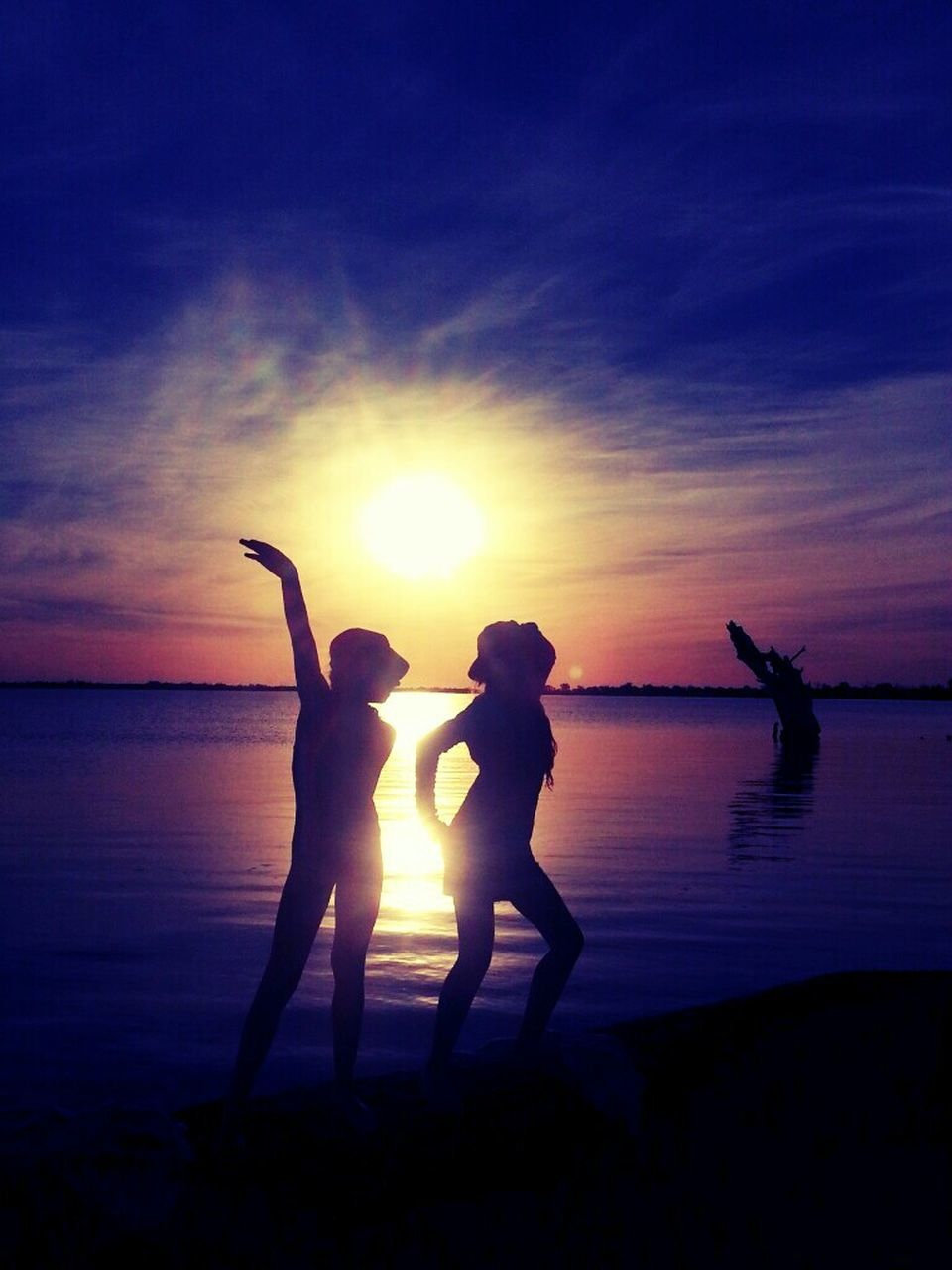 Silhouette Women Posing At Sea Shore Against Sky During Sunset