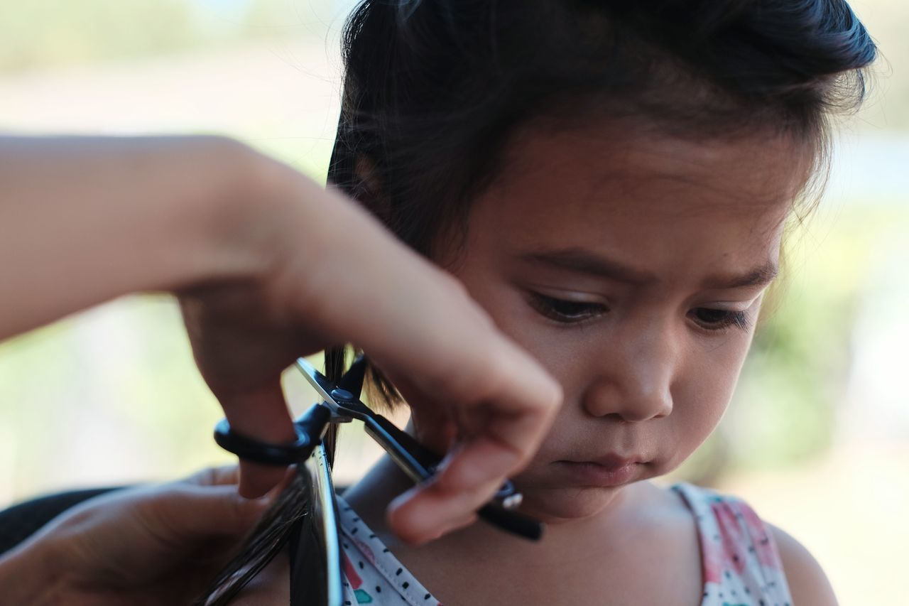 Close up on cute 3 year old girl getting a haircut at home Only Women One Woman Only Headshot Two People Close-up Day Front View Beautiful Woman Outdoors Holding Scissors Hair Haircut Hairstyle Human Body Part Apprehension Gravity 3 Years Old Girl