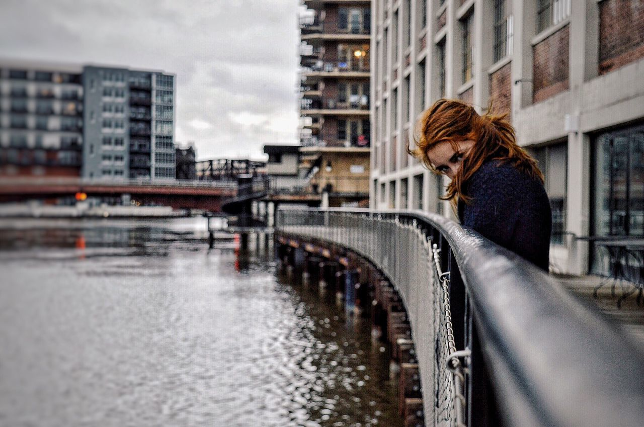 redhead, one person, architecture, built structure, young adult, building exterior, water, outdoors, young women, city, side view, day, one young woman only, bridge - man made structure, beautiful woman, sky, real people, one woman only, women, adult, only women, warm clothing, adults only, people