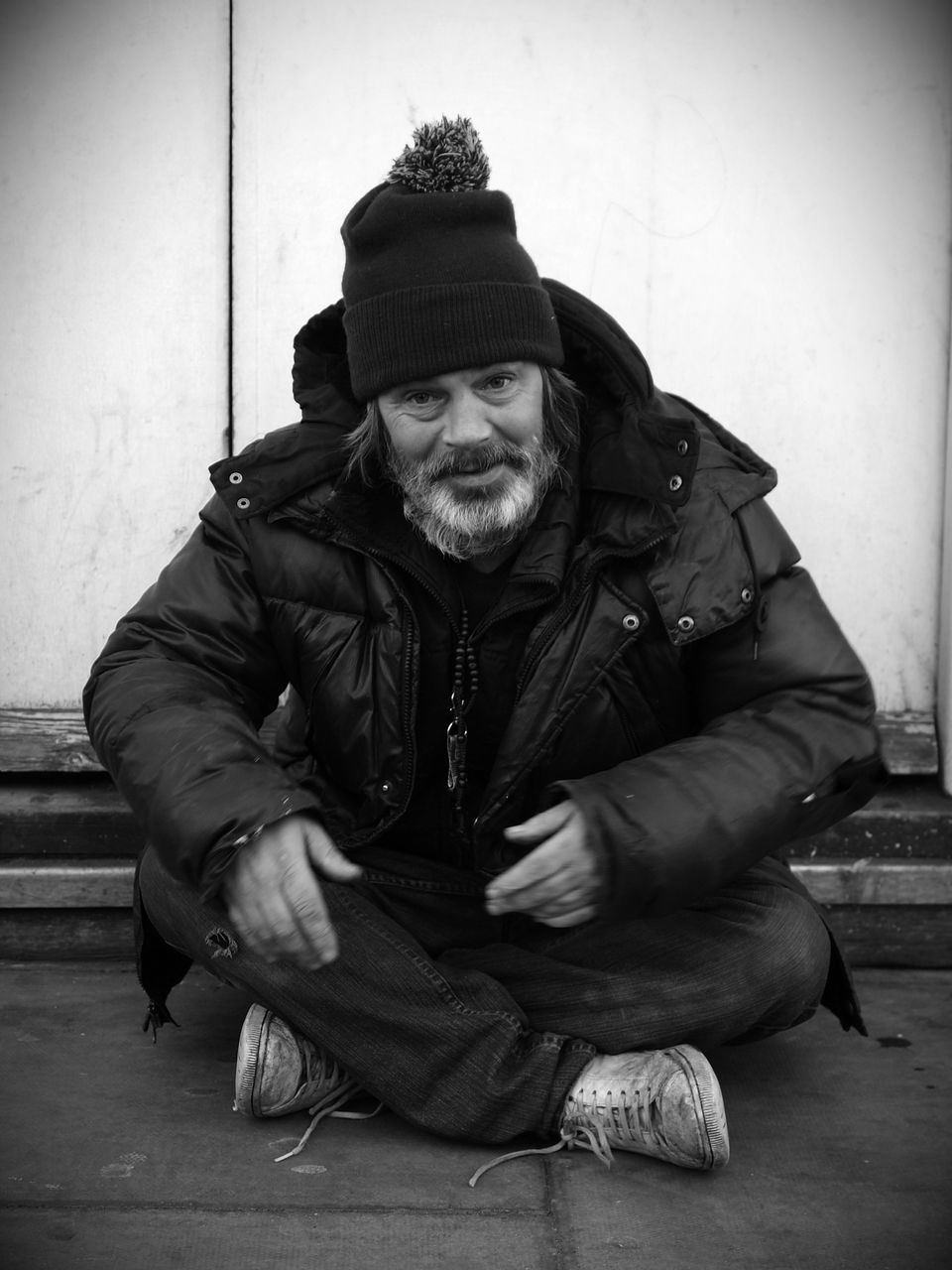 sitting, real people, one person, jacket, knit hat, full length, lifestyles, senior adult, front view, beard, senior men, looking at camera, outdoors, cap, portrait, warm clothing, happiness, day, city, people