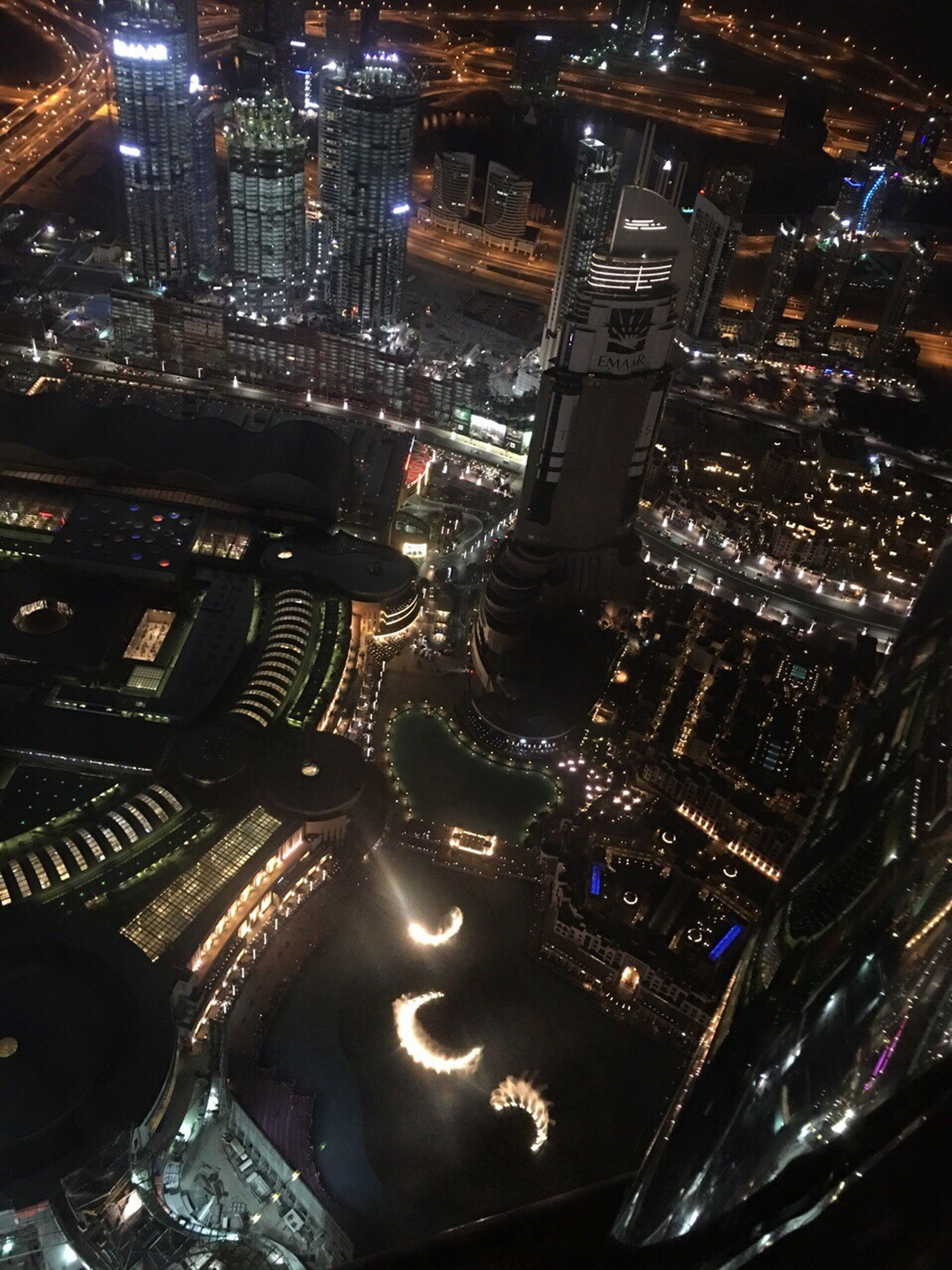 architecture, illuminated, building exterior, city, night, cityscape, built structure, high angle view, crowded, aerial view, city life, skyscraper, tall - high, tower, capital cities, residential district, street, road, office building, residential building