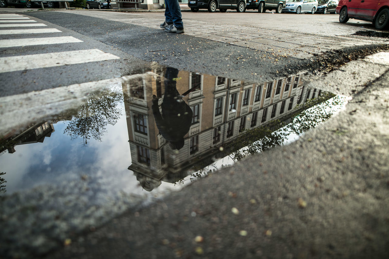 Reflection Of Man In Puddle By Zebra Crossing While Walking On Road