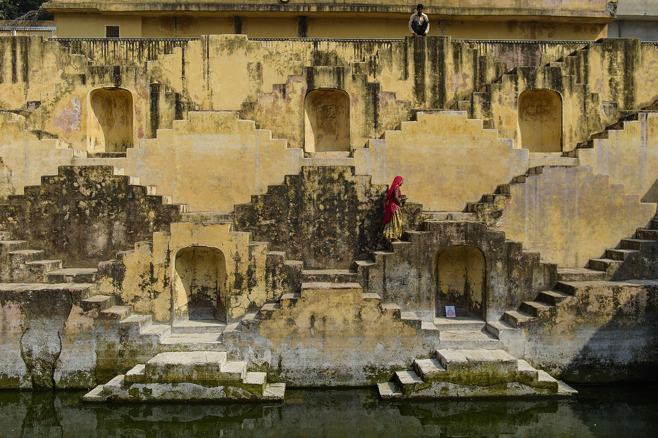 A women crossing the stepwell in Pann Meena Ka Kund, Jaipur, India. Ancient Architecture Building Exterior Built Structure Full Frame Historic History India Outdoors Panna Meena Ka Kund People Steps And Staircases The Past Wall - Building Feature Weathered