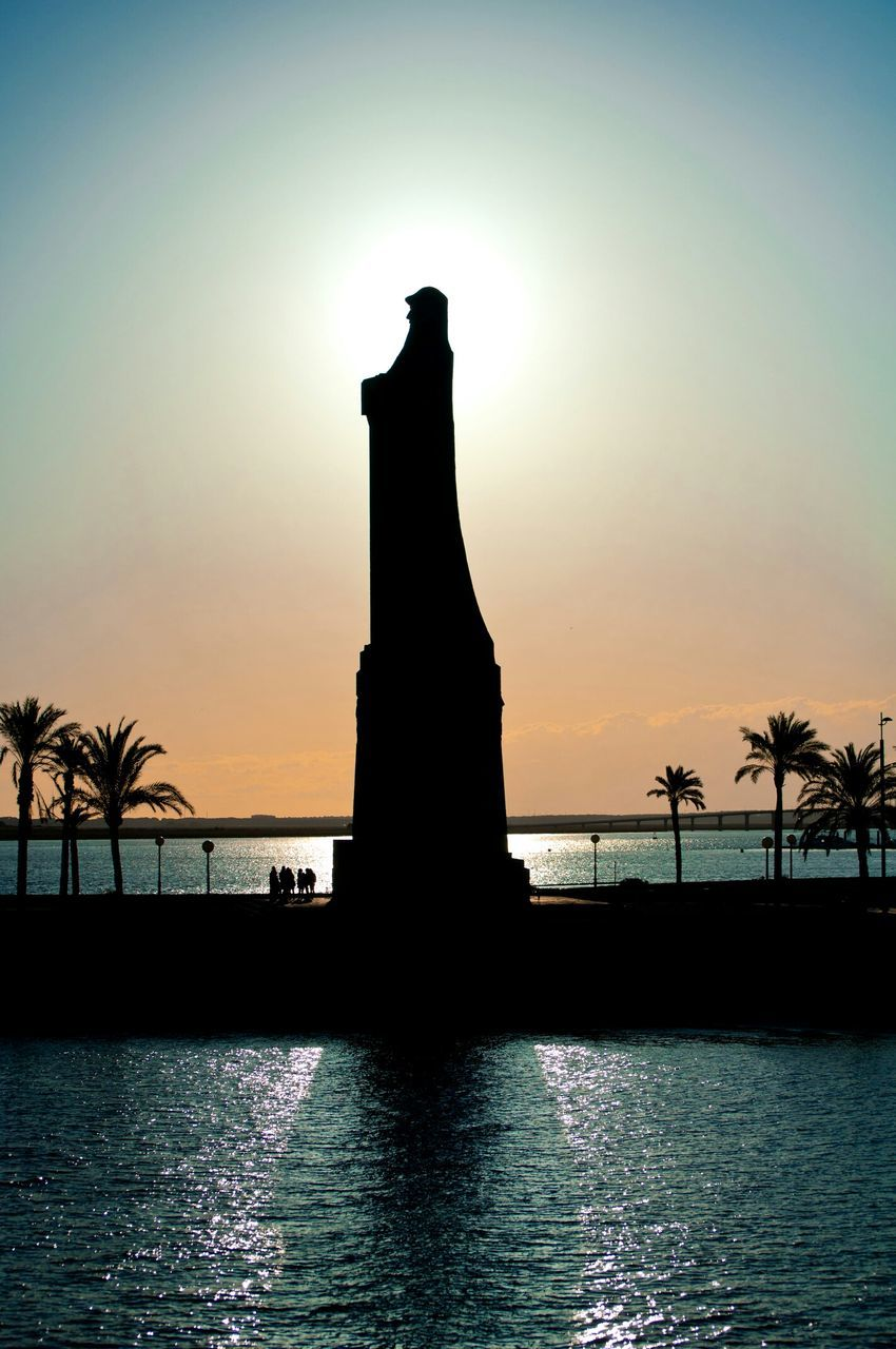 silhouette, sunset, statue, water, travel destinations, sky, sun, no people, outdoors, sea, tranquility, beauty in nature, scenics, sculpture, nature, palm tree, architecture, tree, day
