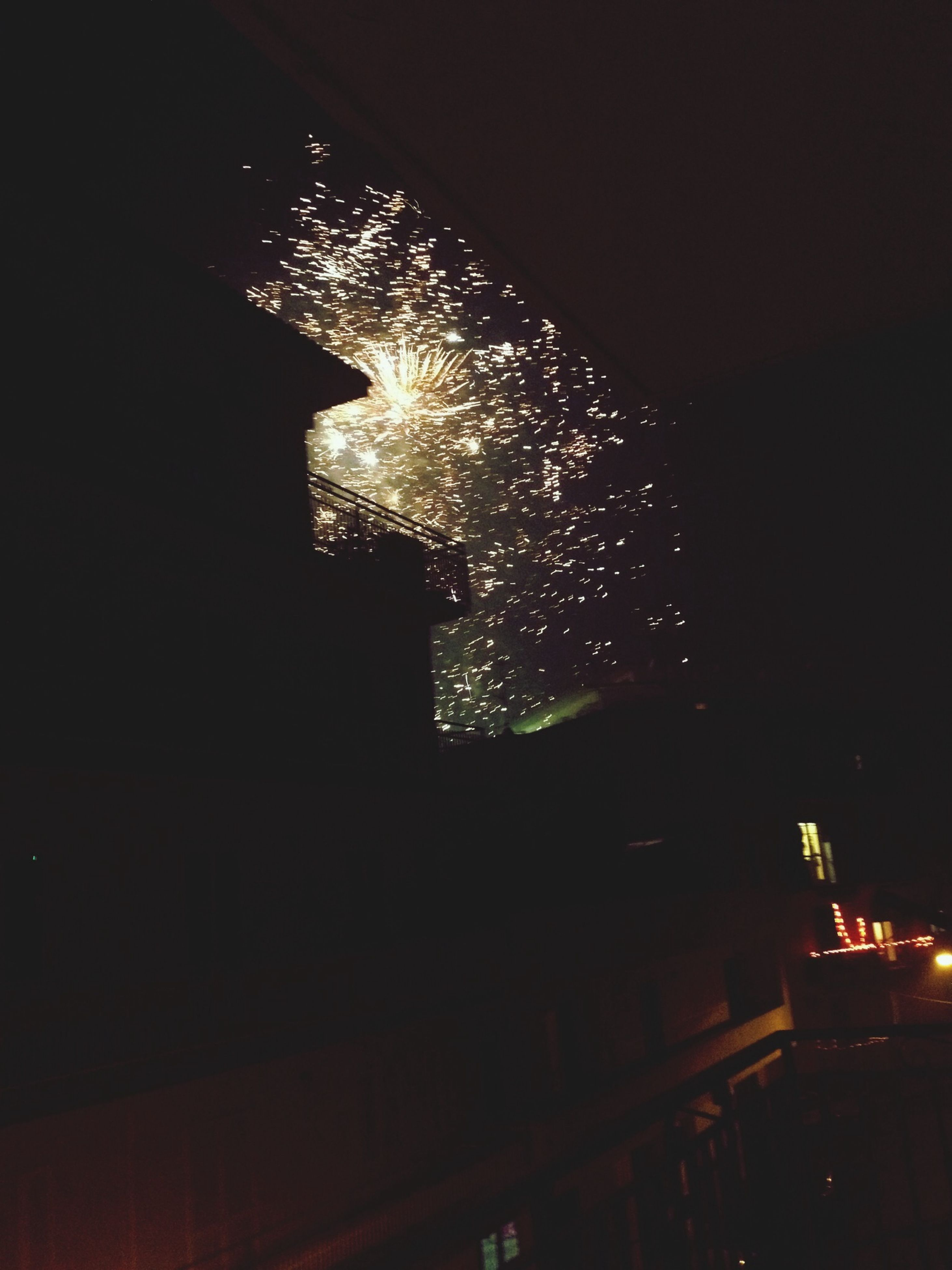 night, illuminated, glowing, building exterior, low angle view, architecture, lighting equipment, built structure, light - natural phenomenon, dark, city, firework display, celebration, long exposure, sky, motion, arts culture and entertainment, exploding, no people, street light