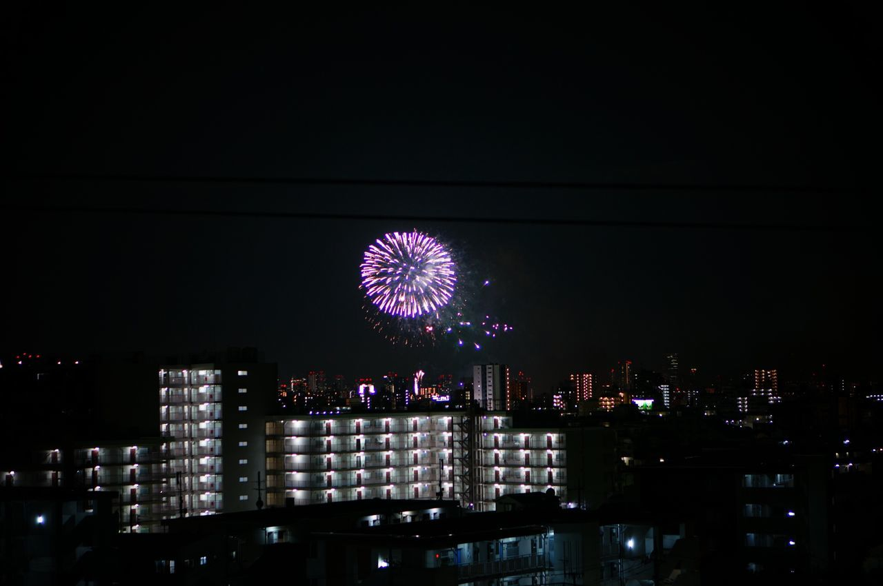 night, illuminated, cityscape, firework display, building exterior, architecture, city, firework - man made object, celebration, skyscraper, sky, built structure, low angle view, motion, no people, outdoors, urban skyline