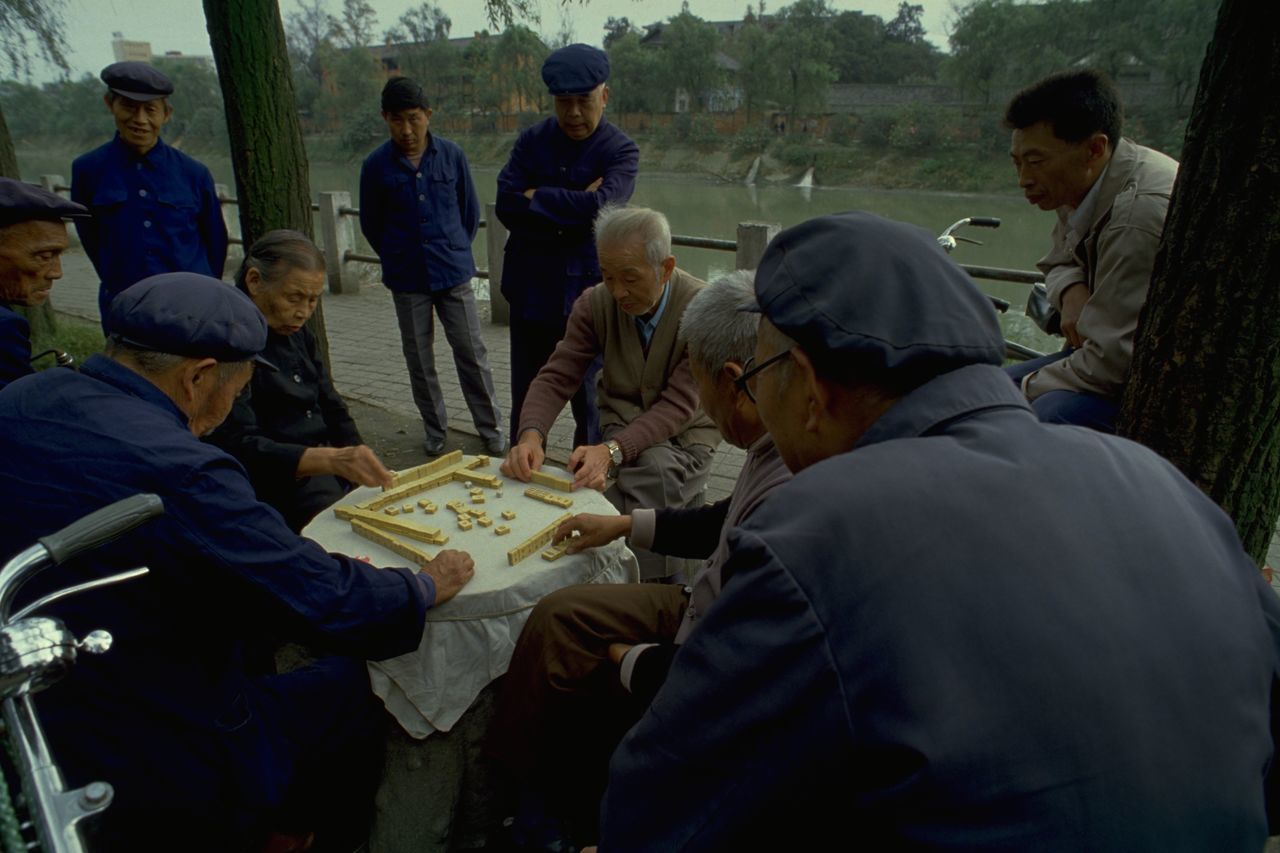 Mahjong In Guangzhou Old People in Mao Suits Playing Mahjong in Guangzhou, China. Commonly played by four players, Mahjong originated in China during the Qing dynasty. The game is played with a set of 144 tiles, based on Chinese characters and symbols. Each player is given 13 tiles at the start, taking it in turns to draw and discard a fourteenth tile to try and make a winning hand of four melds (three identical tiles) and an eye (a pair of identical tiles). Of course, Mahjong is a little more complicated than that, but it was interesting to watch these Chinese players continue an age-old tradition; when on a photo walkabout in Guangzhou, China. Open-air games often attract a little crowd of onlookers, and the occasional foreign tourist posing as a travel photographer. What made this picture special for me was the captivating look on these old Chinese faces; and their clothing. These dark blue tunics were originally known as the Zhongshan suit, after Sun Yat-sen (also called Sun Zhongshan) helped revolutionise China and overthrow the the Qing (or Manchu) dynasty in the early 20th century. Sometimes called the 'father of modern China', Zhongshan is credited with giving the suit its symbolisms. The four pockets on the front represent the Four Virtues: politeness, justice, honesty, and a sense of shame. The five buttons on the front then represent the five branches of government in the constitution of the Republic of China. The three buttons on the cuff represent Sun's Three Principles of the People: nationalism, democracy, and people's livelihood. The 'blue look' was later made famous by Mao Zedong and the tunic subsequently became known as a 'Mao suit'. http://pics.travelnotes.org/ ASIA Authentic Blue Caps China Green Guangzhou Landscape Local Mahjong Mao Suits Maximum Closeness Michel Guntern Old Lady Old Men People People Watching Real People Riverside Let's Go. Together. Table Games Travel Travel Photography Travel Photos Travel Pics