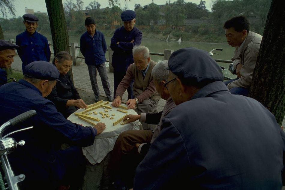 Mahjong In Guangzhou Old People in Mao Suits Playing Mahjong in Guangzhou, China. Commonly played by four players, Mahjong originated in China during the Qing dynasty. The game is played with a set of 144 tiles, based on Chinese characters and symbols. Each player is given 13 tiles at the start, taking it in turns to draw and discard a fourteenth tile to try and make a winning hand of four melds (three identical tiles) and an eye (a pair of identical tiles). Of course, Mahjong is a little more complicated than that, but it was interesting to watch these Chinese players continue an age-old tradition; when on a photo walkabout in Guangzhou, China. Open-air games often attract a little crowd of onlookers, and the occasional foreign tourist posing as a travel photographer. What made this picture special for me was the captivating look on these old Chinese faces; and their clothing. These dark blue tunics were originally known as the Zhongshan suit, after Sun Yat-sen (also called Sun Zhongshan) helped revolutionise China and overthrow the the Qing (or Manchu) dynasty in the early 20th century. Sometimes called the 'father of modern China', Zhongshan is credited with giving the suit its symbolisms. The four pockets on the front represent the Four Virtues: politeness, justice, honesty, and a sense of shame. The five buttons on the front then represent the five branches of government in the constitution of the Republic of China. The three buttons on the cuff represent Sun's Three Principles of the People: nationalism, democracy, and people's livelihood. The 'blue look' was later made famous by Mao Zedong and the tunic subsequently became known as a 'Mao suit'. http://pics.travelnotes.org/ ASIA Authentic Blue Caps China Green Guangzhou Landscape Local Mahjong Mao Suits Maximum Closeness Michel Guntern Old Lady Old Men People People Watching Real People Riverside Snap A Stranger Table Games Travel Travel Photography Travel Photos Travel Pics