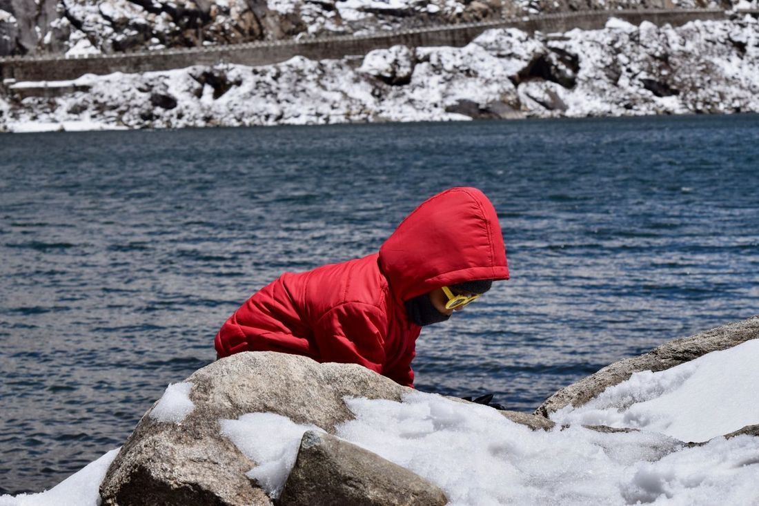View of kid playing at lake Beauty In Nature Changu Lake Childhood Close-up Day Lake Leisure Activity Lifestyles Nature One Person Outdoors People Real People Red Retaining Wall Rock - Object Sea Standing Tsomgo Lake Tsonga Water