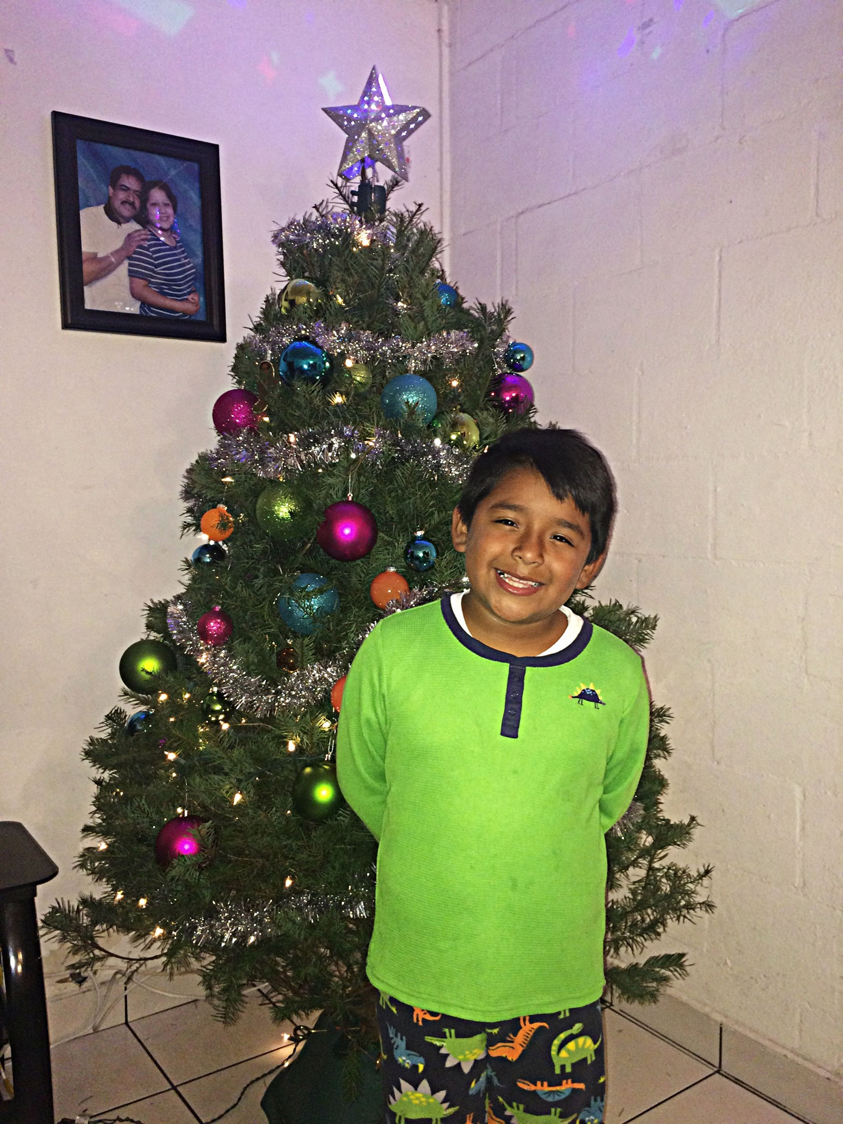 portrait, looking at camera, childhood, indoors, front view, elementary age, lifestyles, celebration, leisure activity, person, smiling, standing, wall - building feature, decoration, happiness, boys, casual clothing, multi colored