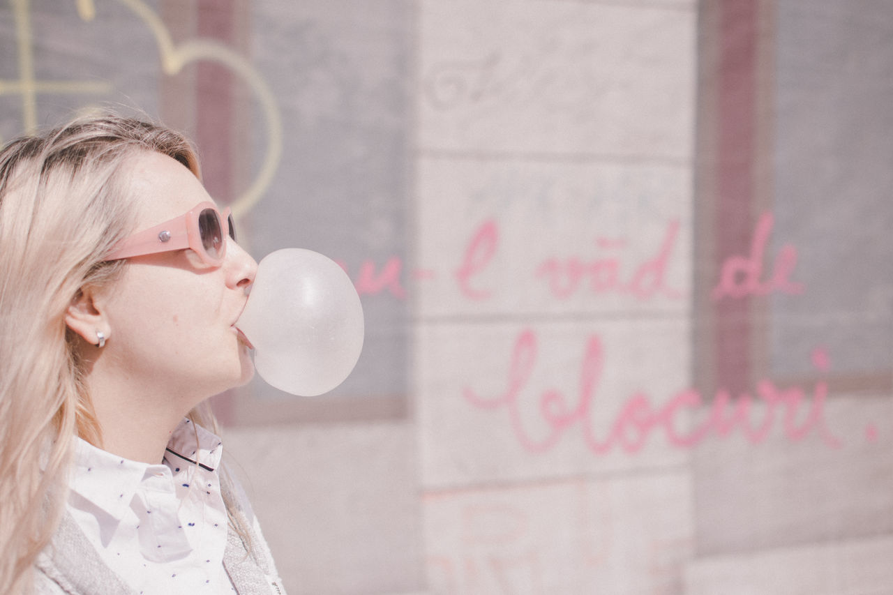 Side View Of Woman Blowing Bubble Gum By Glass Window
