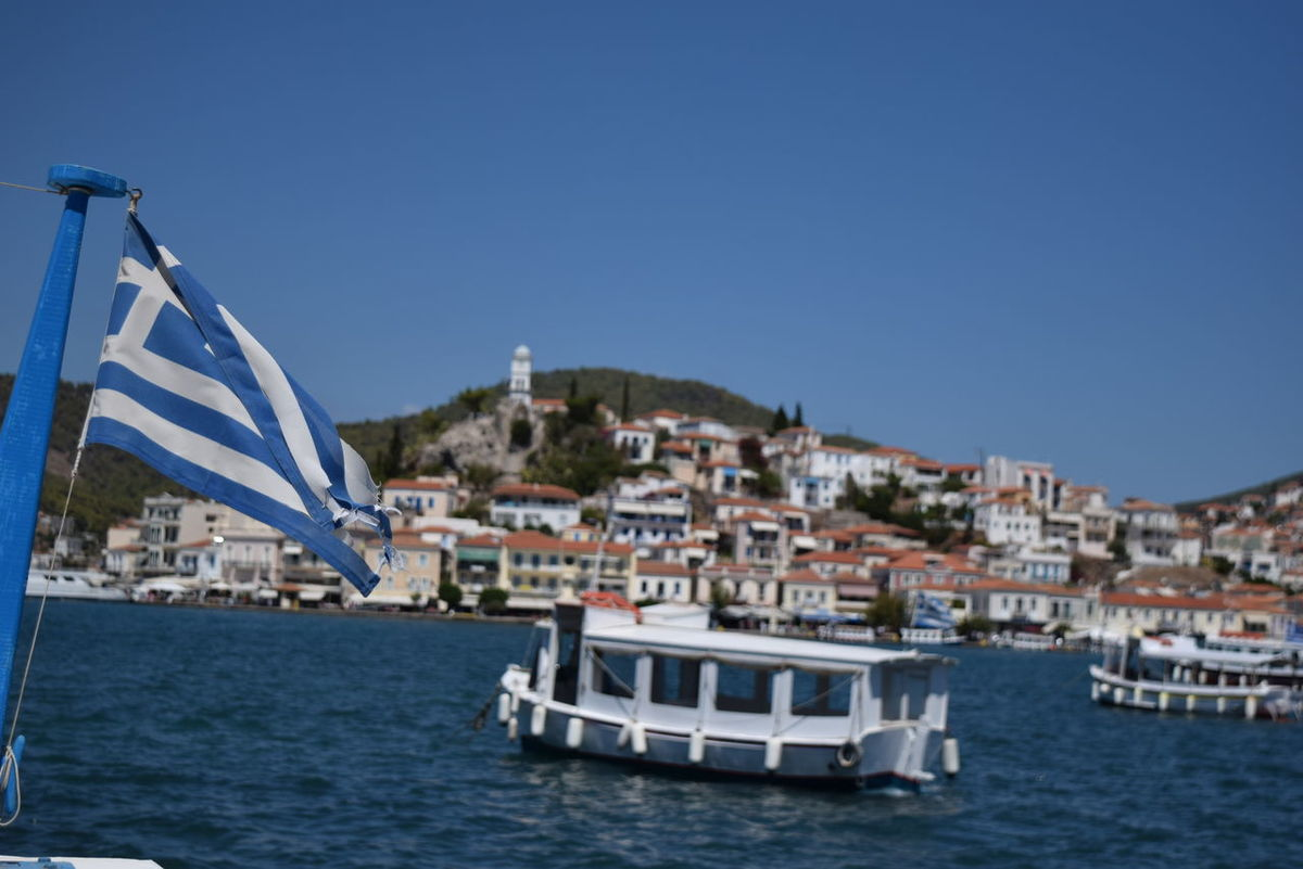 Architecture Blue Boat Built Structure City Cityscape Clear Sky Day Mode Of Transport Nature Nautical Vessel No People Ocean Outdoors Poros Residential District Rippled Sailing Sea Ship Sky Town Travel Destinations Water Waterfront