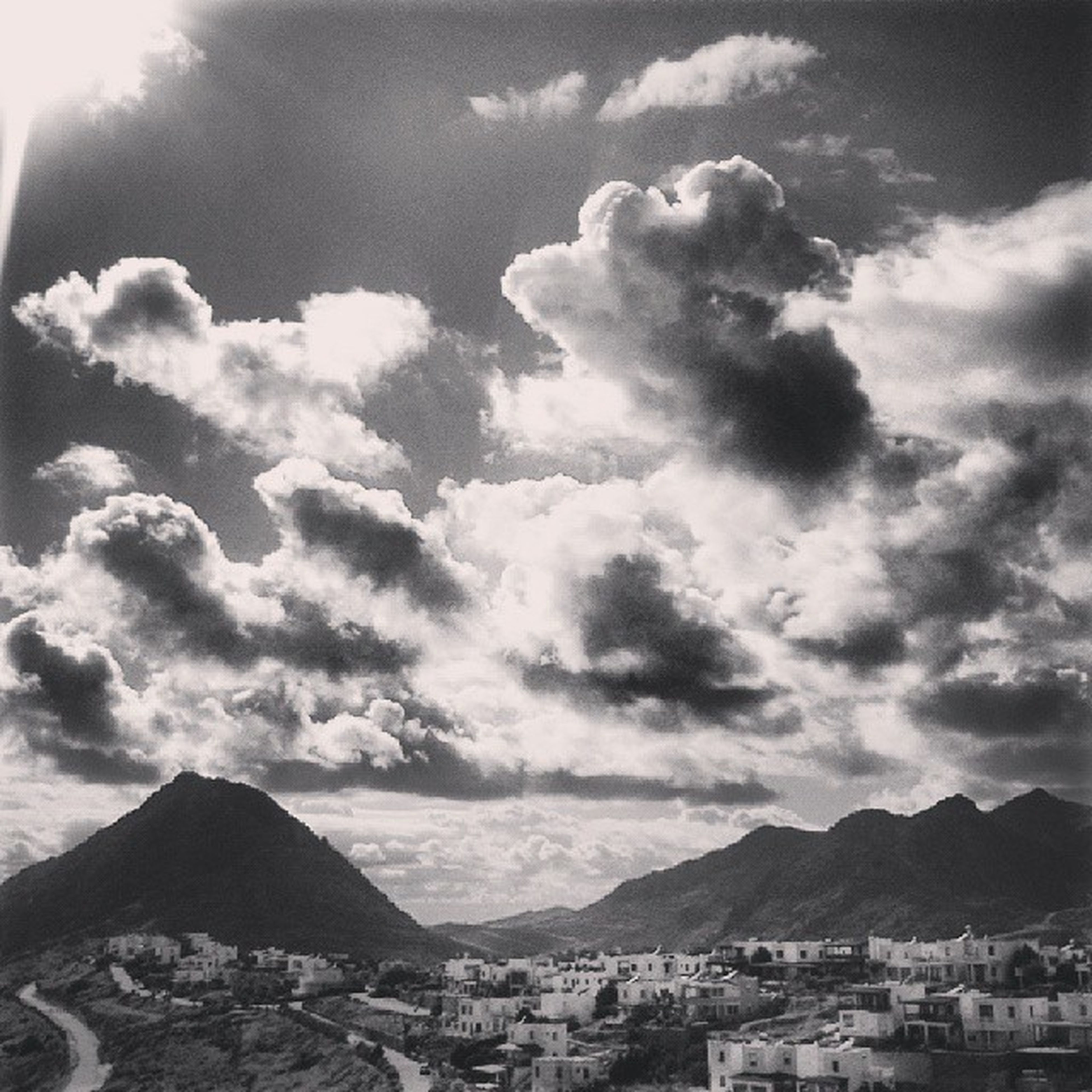 mountain, sky, building exterior, mountain range, architecture, cloud - sky, built structure, cloudy, cloud, scenics, town, house, beauty in nature, nature, residential structure, city, residential building, cityscape, residential district, townscape