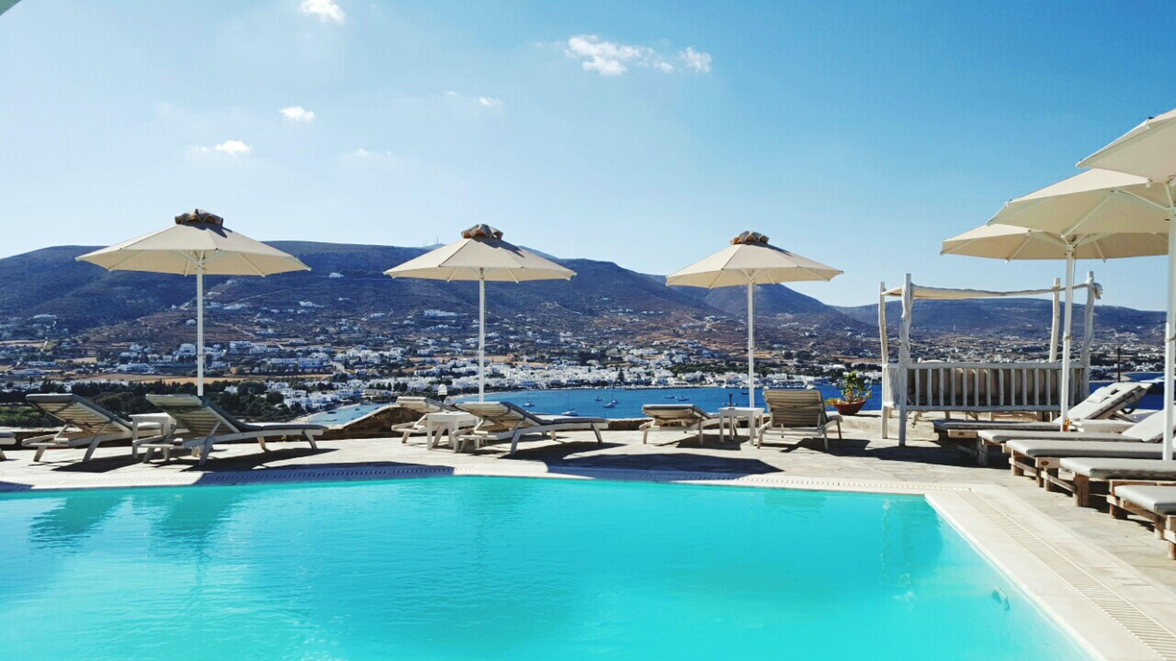 sunshade, water, beach umbrella, sky, parasol, blue, swimming pool, sea, tranquility, tranquil scene, sunny, cloud - sky, waterfront, day, travel destinations, nature, outdoors, scenics, summer, beauty in nature, repetition, mountain, vacations