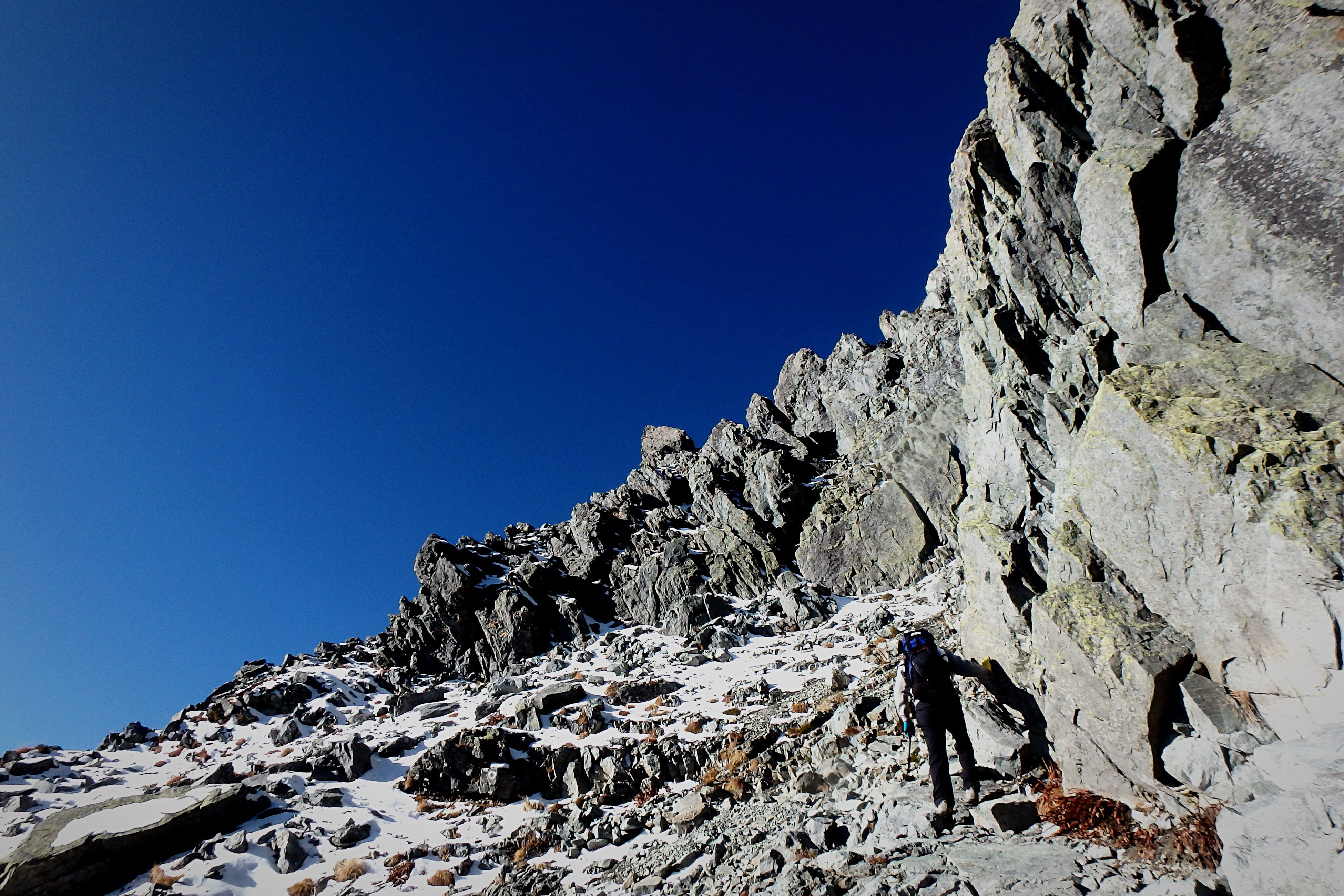 clear sky, blue, copy space, mountain, low angle view, rock formation, tranquility, rock - object, tranquil scene, beauty in nature, scenics, nature, sunlight, rocky mountains, landscape, day, physical geography, non-urban scene, snow, cliff