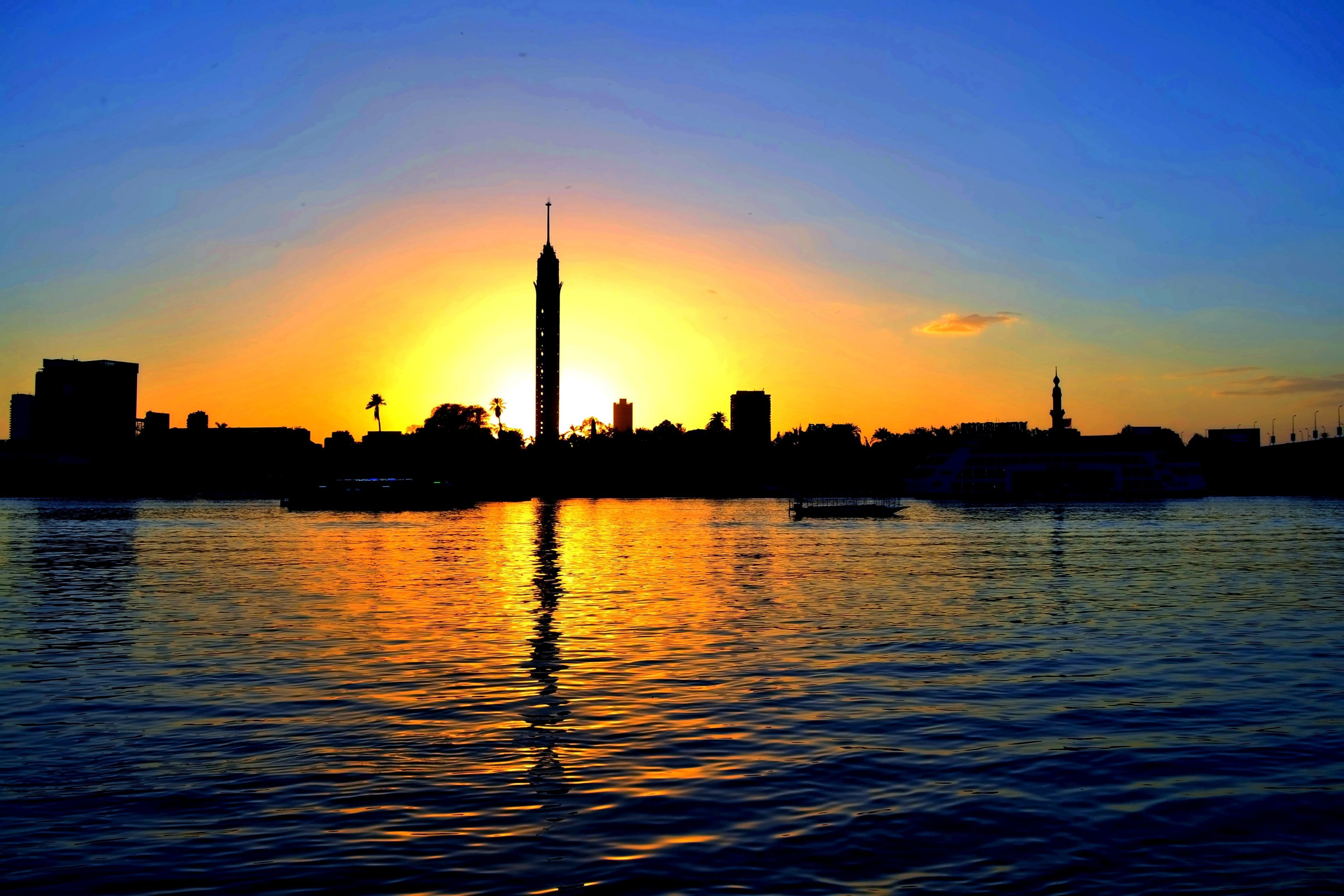 sunset, city, reflection, silhouette, architecture, building exterior, water, sky, travel destinations, urban skyline, waterfront, built structure, no people, skyscraper, outdoors, cityscape, romantic sky, nature, beauty in nature, day