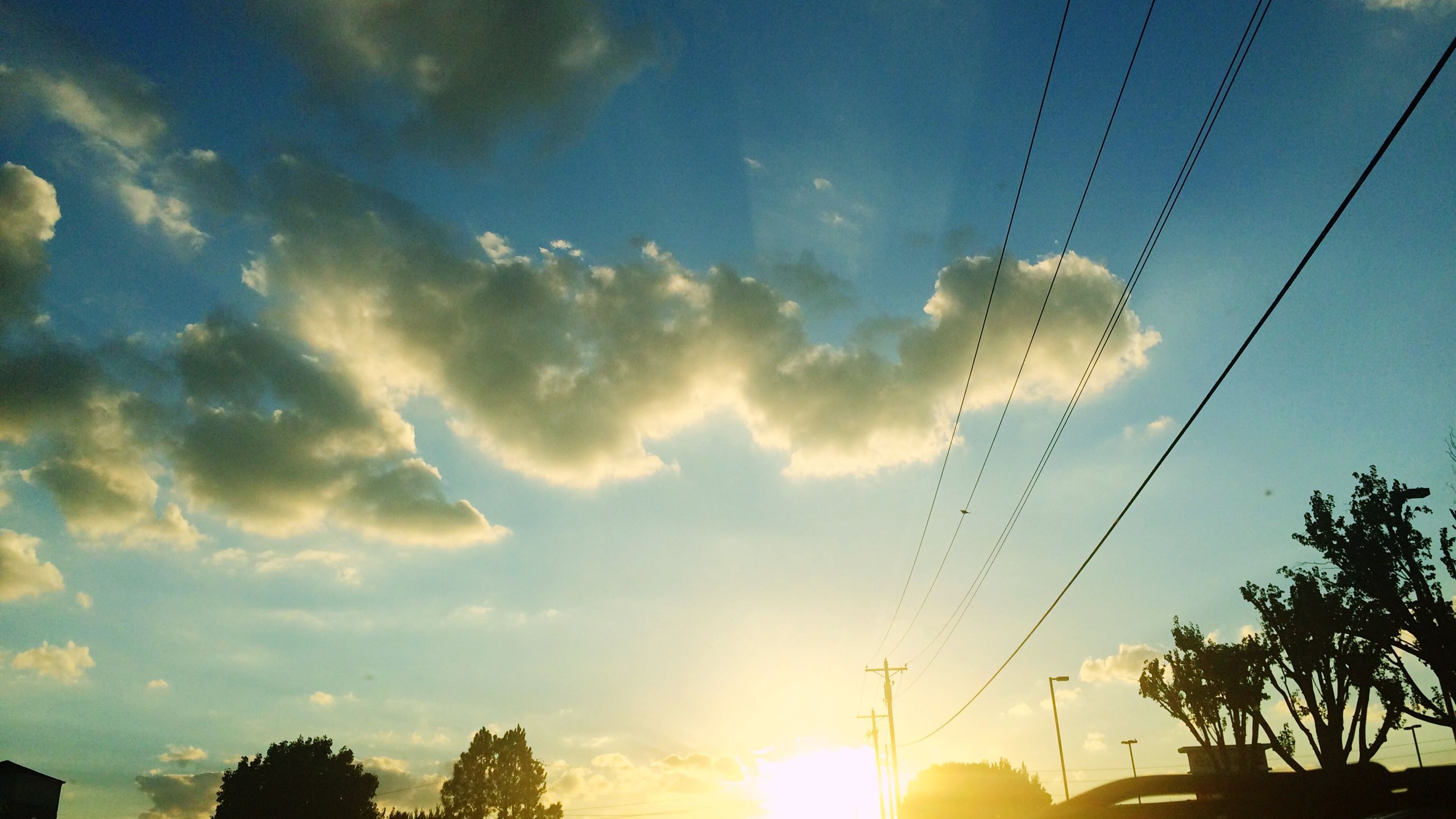 low angle view, sky, silhouette, power line, sunset, tree, electricity pylon, electricity, cable, street light, sun, cloud - sky, nature, built structure, outdoors, beauty in nature, sunlight, cloud, no people, power supply