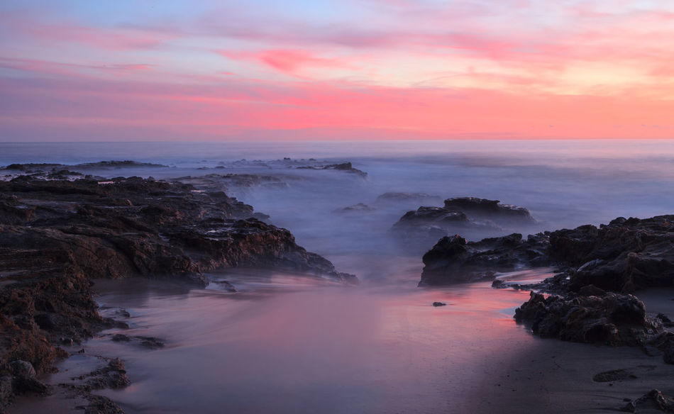 Sunset over the rocks at Shaws Cove in Laguna Beach as water flows over the stone Beach Beauty In Nature Dramatic Sky Horizon Over Water Laguna Beach, CA Nature No People Outdoors Scenics Sea Shaws Beach Shaws Cove Sky And Clouds Southern California Sunset Sunsets