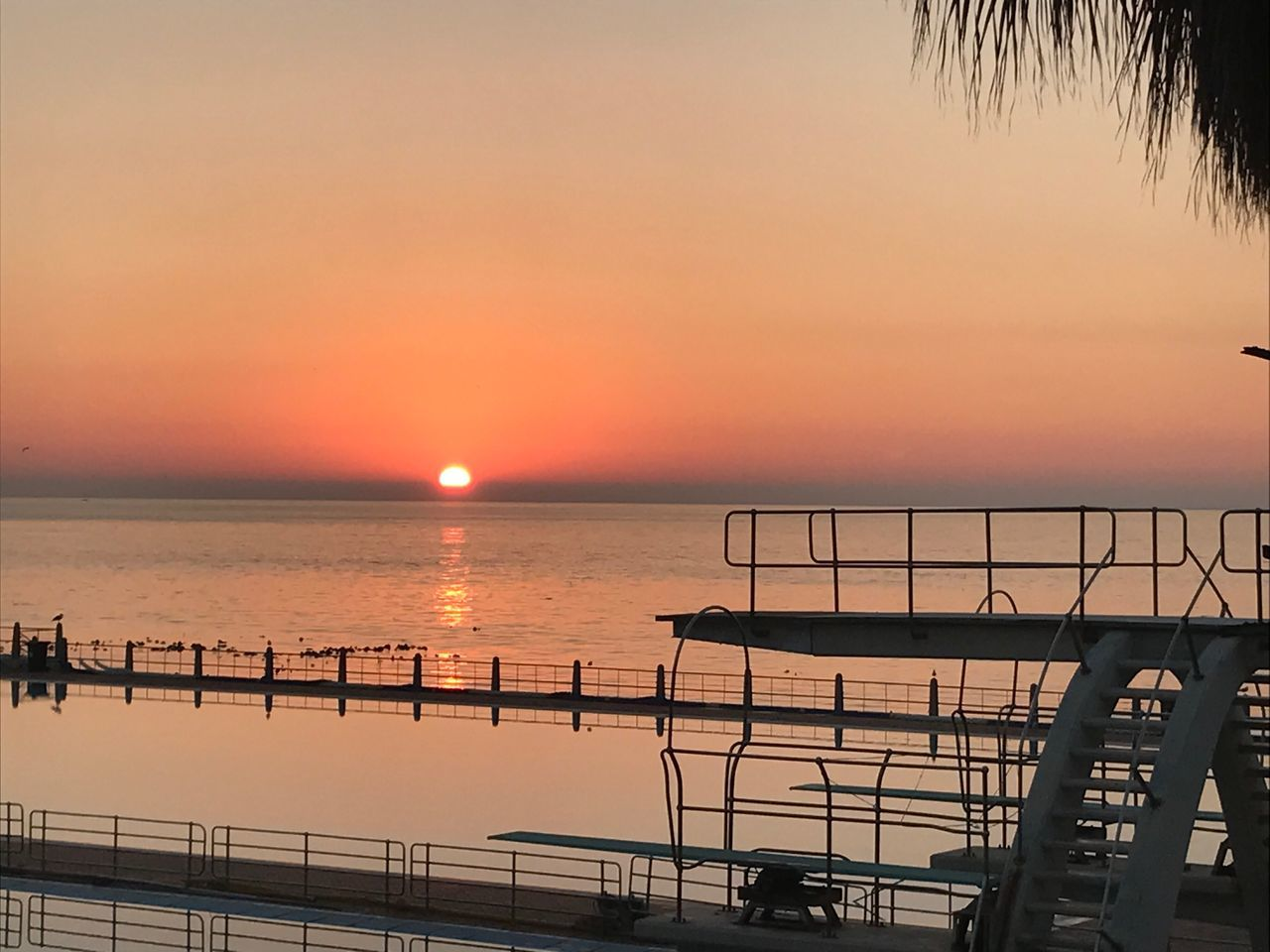 sunset, water, sea, orange color, scenics, beauty in nature, nature, reflection, silhouette, sky, railing, sun, horizon over water, tranquility, tranquil scene, nautical vessel, outdoors, no people, travel destinations, clear sky, tree, day