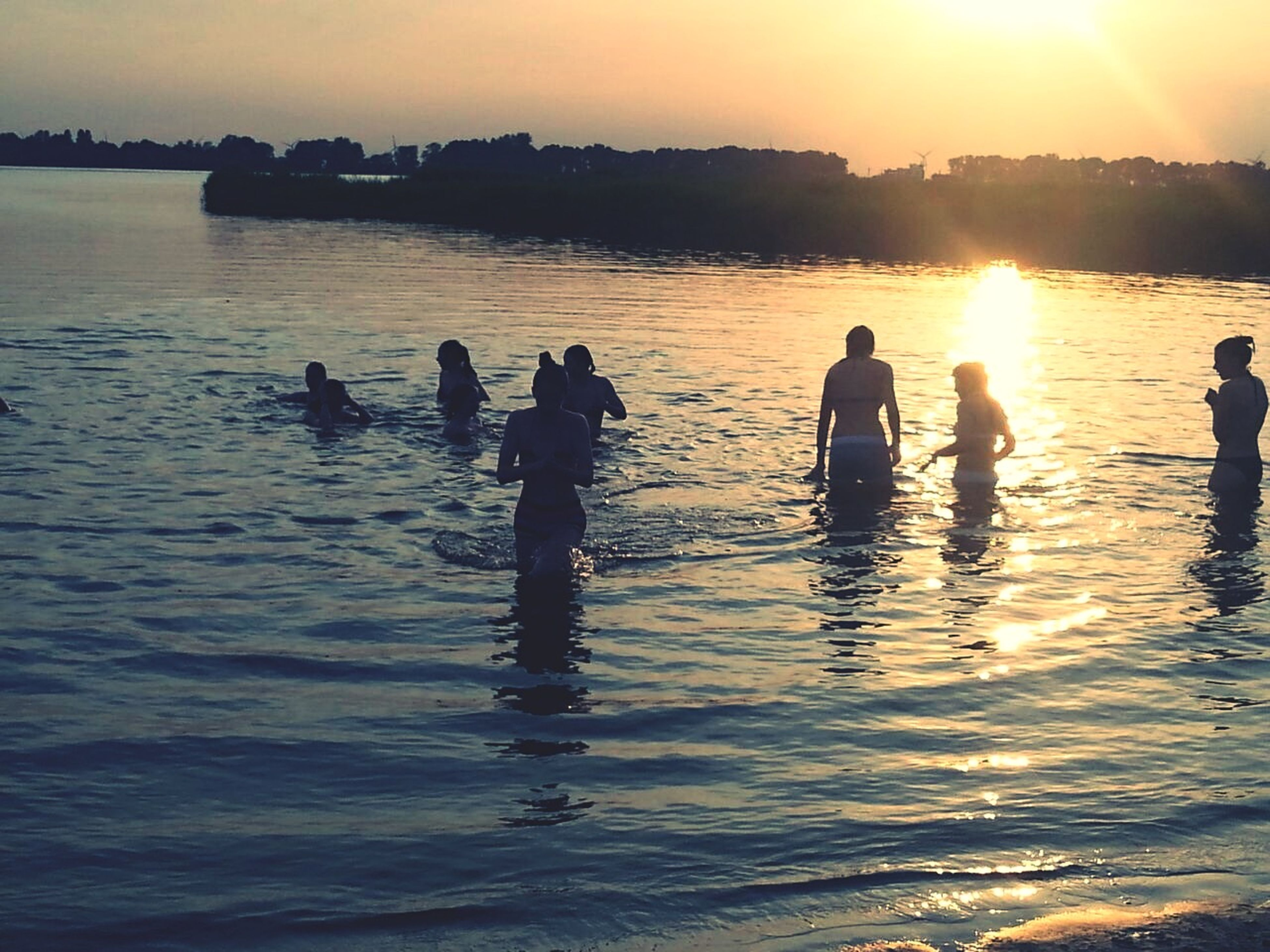 water, sunset, silhouette, reflection, sun, sea, sunlight, leisure activity, lifestyles, men, beauty in nature, nature, scenics, togetherness, sky, tranquility, tranquil scene, beach, lake