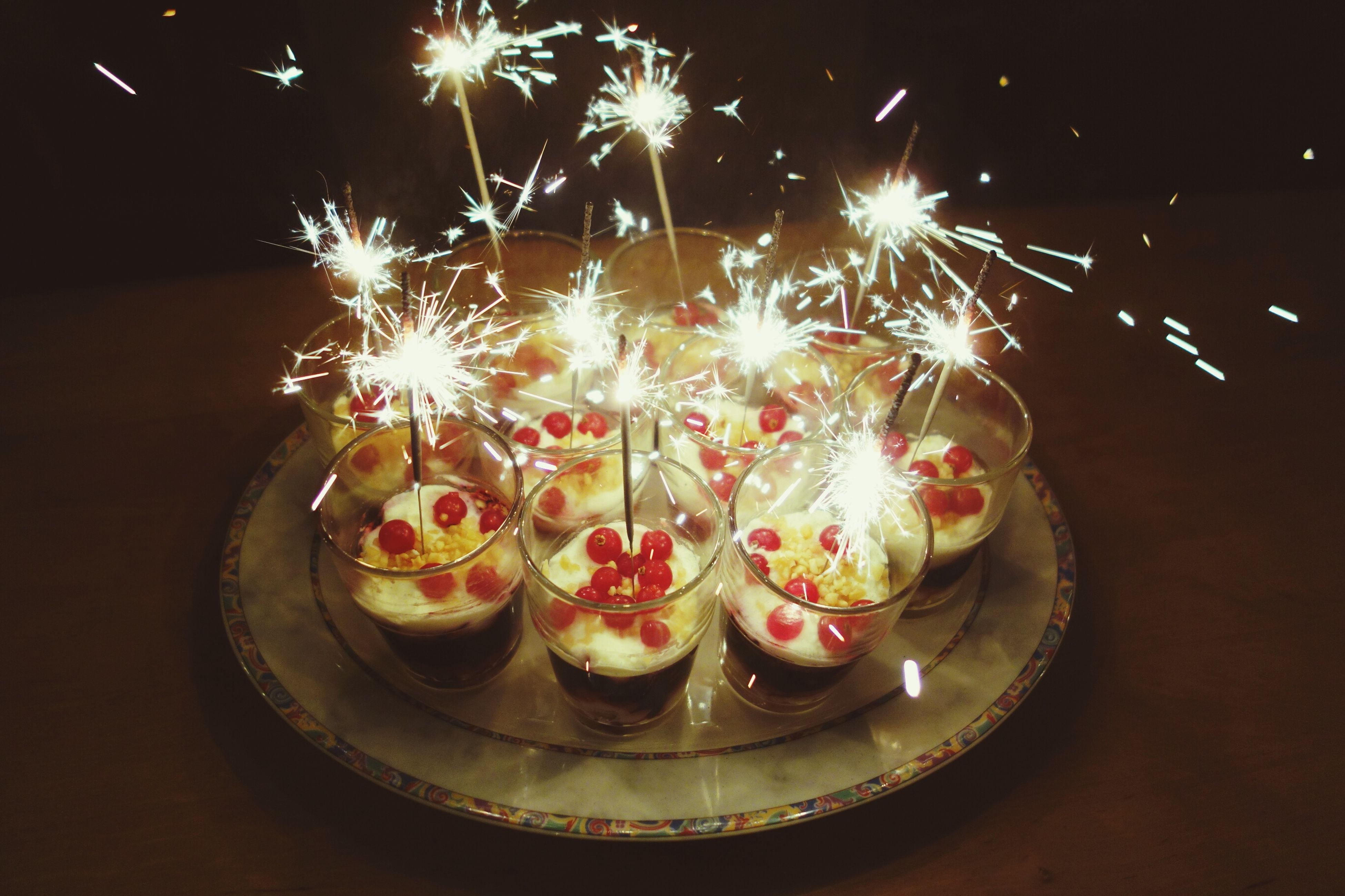 illuminated, celebration, night, indoors, decoration, fire - natural phenomenon, glowing, flame, candle, burning, sweet food, christmas, lit, still life, multi colored, tradition, celebration event, heat - temperature, food, close-up