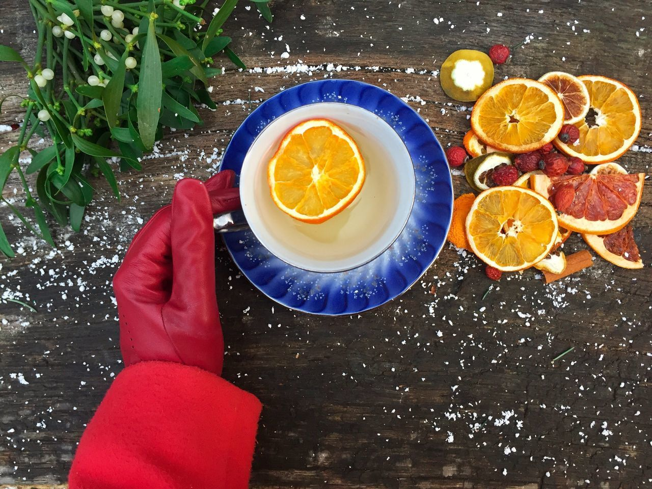 Woman hands wearing red gloves holding mug of orange tea placed on snowy table decorated with mistletoe and orange slices Table One Person Human Hand Day Winter Snow Cold Gloves Red Hand Woman Table Drink Mistletoe Oranges Tea Hot Drink Red Gloves Cup Glass Season  Outdoors Orange Tea EyeEmNewHere