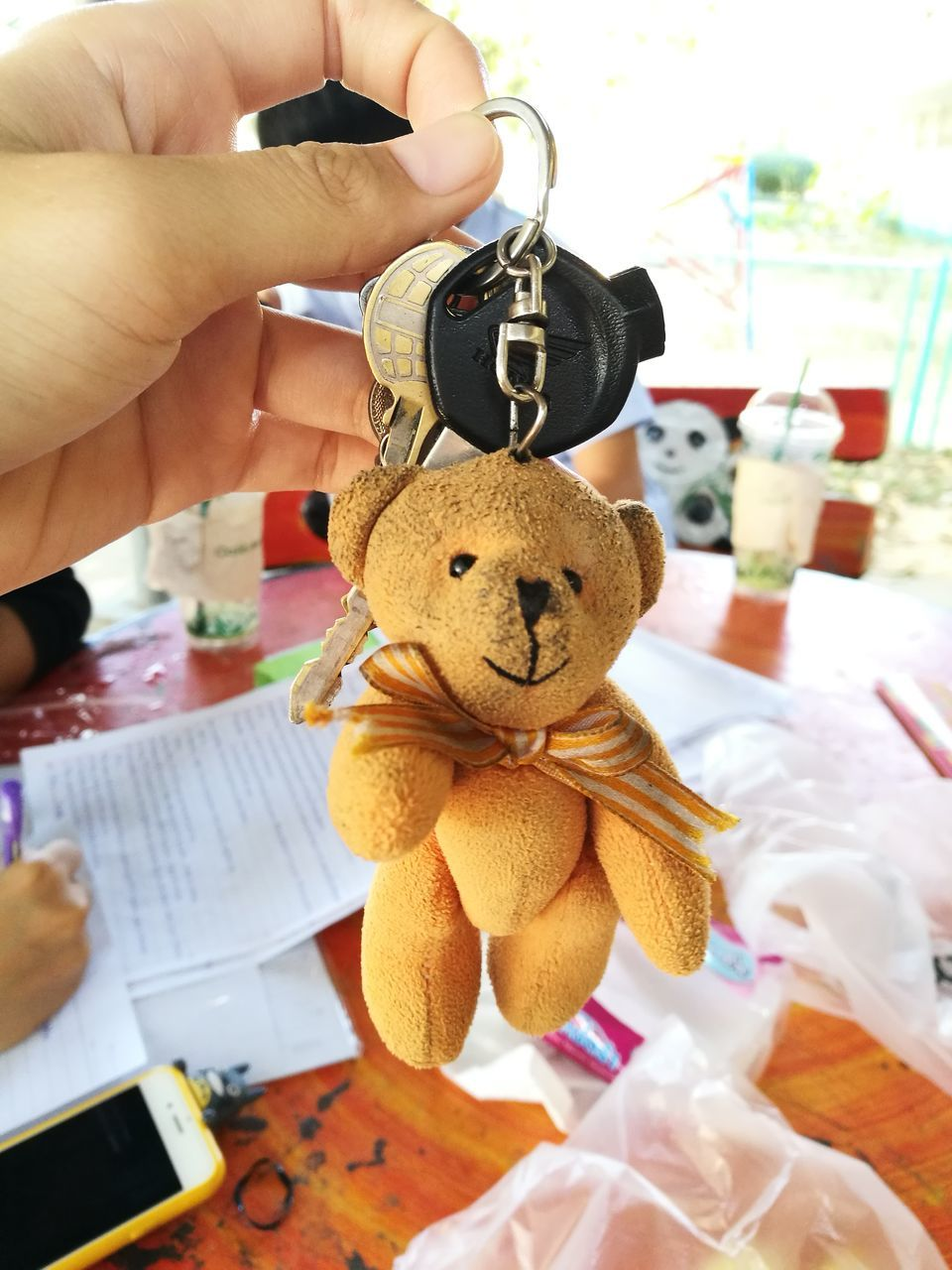 human hand, teddy bear, stuffed toy, toy, one person, human body part, holding, indoors, real people, childhood, close-up, day, people