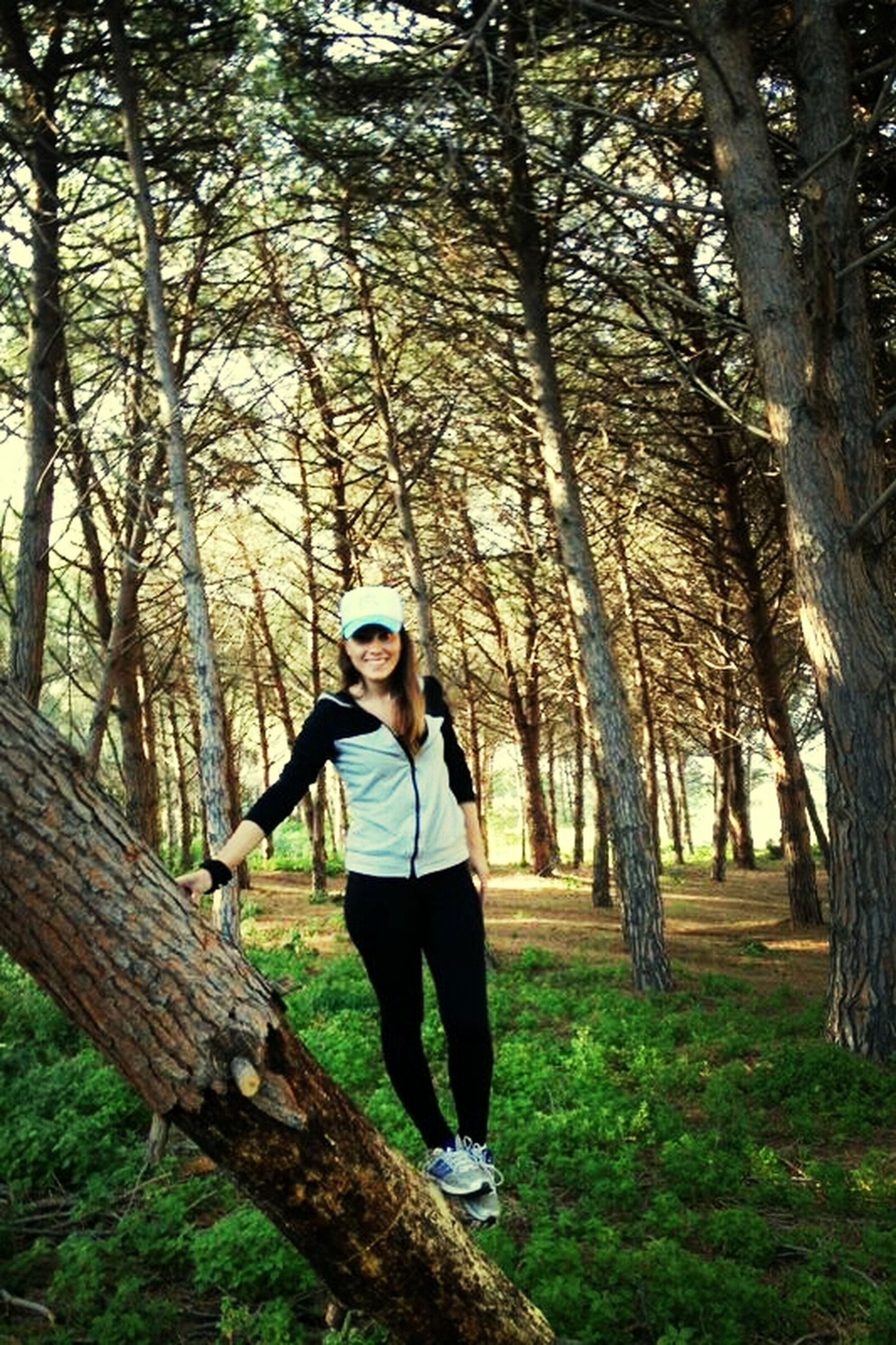 tree, lifestyles, young adult, casual clothing, tree trunk, person, leisure activity, forest, full length, looking at camera, front view, portrait, standing, young women, smiling, branch, happiness, growth