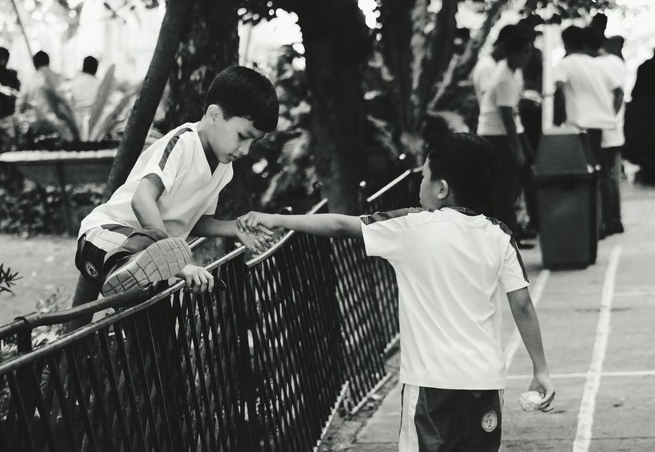 BROTHERS: Helping Hand Child Playing Two People Men Outdoors Real People Day People Crowd Streetphotography Black And White Adult Blackandwhite Photography Cebu Only Men Blacknwhite Kids Play Kids Playing Kids Having Fun Kids Are Awesome