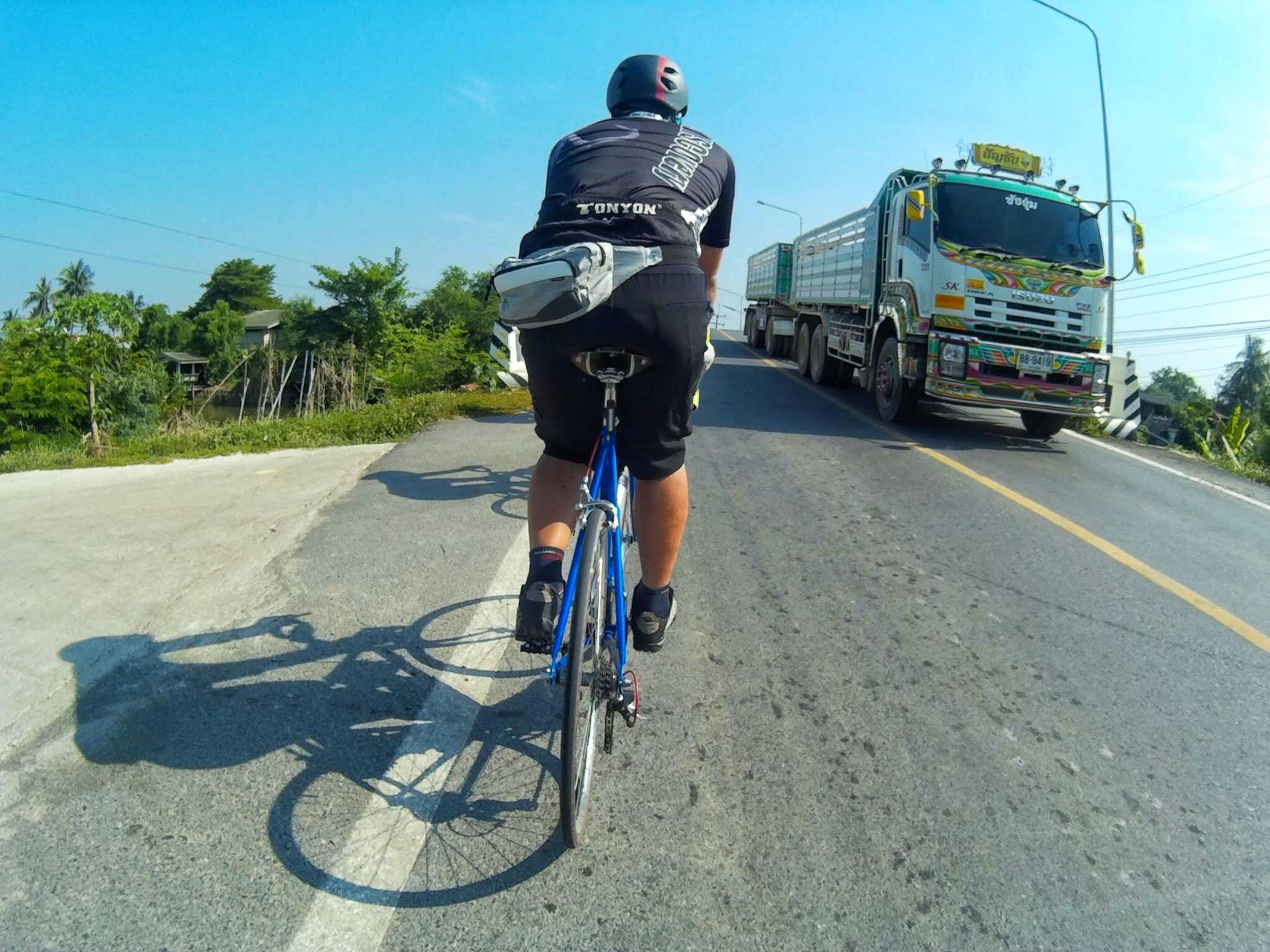 transportation, land vehicle, mode of transport, road, street, car, bicycle, men, riding, clear sky, lifestyles, sunlight, tree, full length, the way forward, travel, leisure activity, day