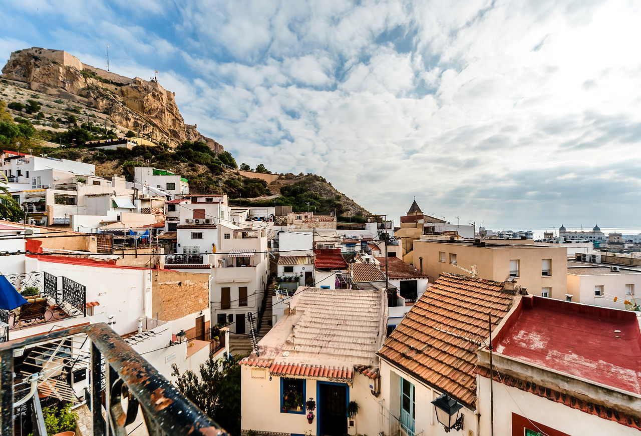 Rooftops of Alicante city. Mount Benacantil with the Castle of Santa Barbara (Castillo de Santa Barbara)- fortification in the centre of Alicante city. Valencia, Spain Mount Becantil Above Aerial View Alicante, Spain Architecture Castillo De Santa Bárbara Cityscape Cloudy Sky Costa Blanca Crowded Europe Exterior Fortification Hilltop Houses Landscape Mediterranean Sea Mountain Outdoors Rock Formation Rooftops Scenery Sunlight Travel Destinations València