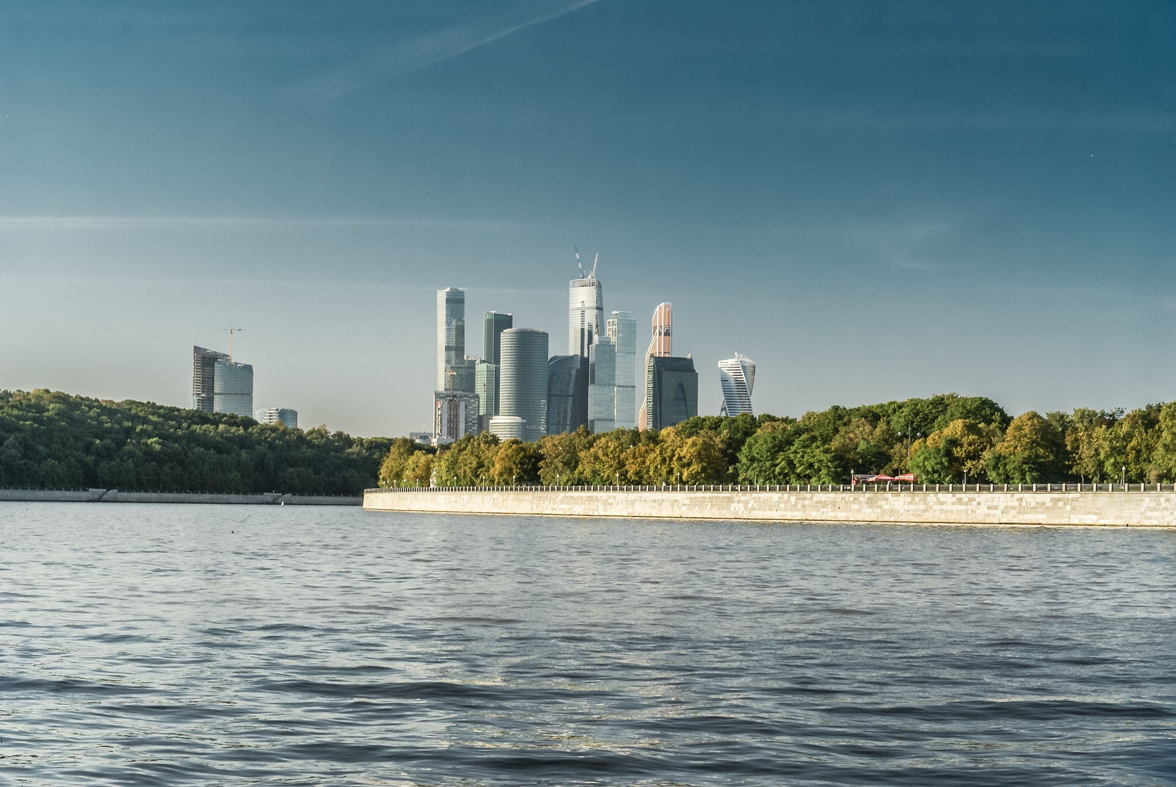 building exterior, architecture, built structure, skyscraper, city, water, tower, tall - high, waterfront, urban skyline, modern, cityscape, sky, office building, river, financial district, tree, blue, travel destinations, skyline