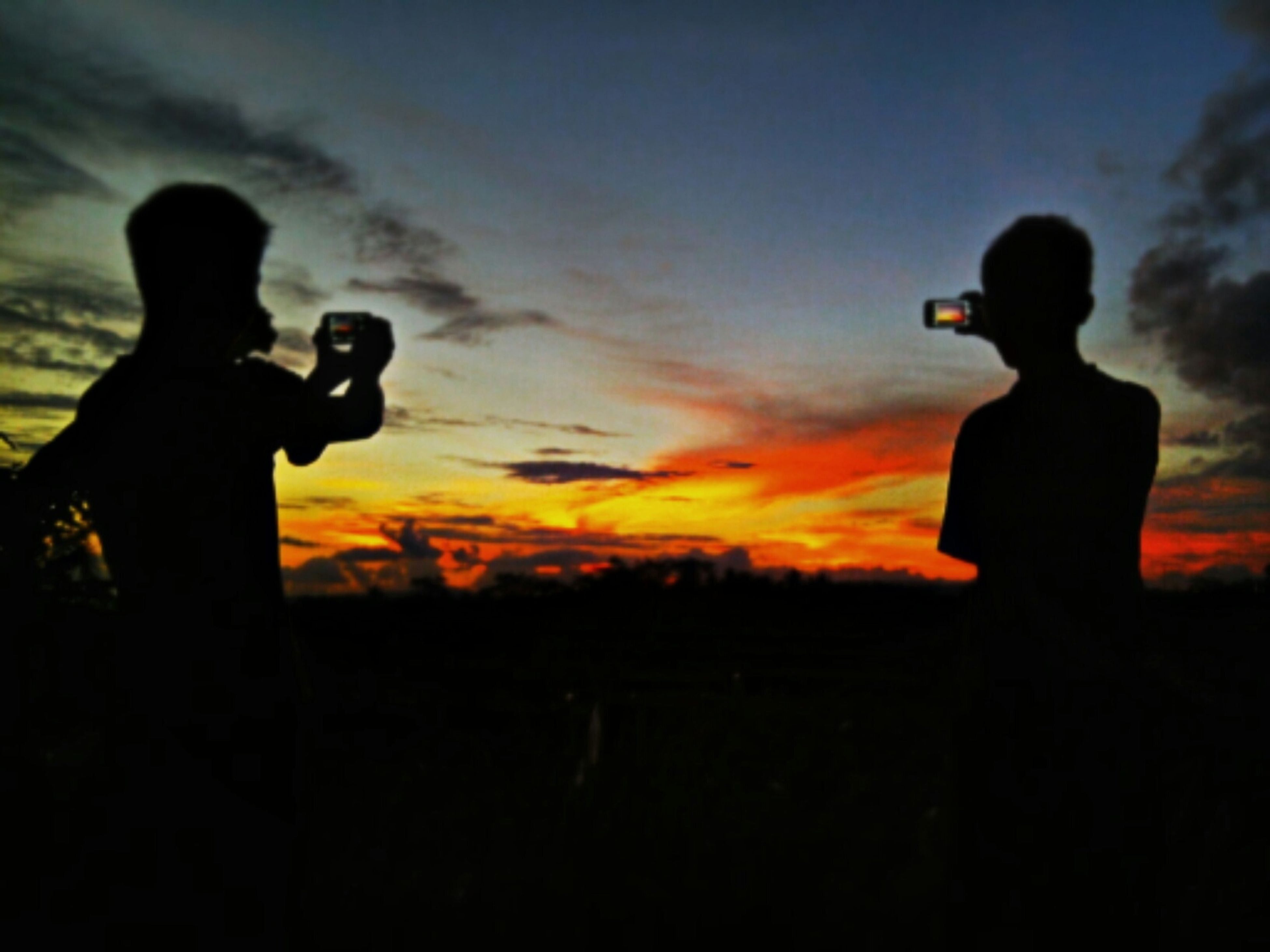 silhouette, sunset, lifestyles, sky, leisure activity, standing, men, three quarter length, cloud - sky, orange color, outline, photography themes, photographing, togetherness, dusk, field, love