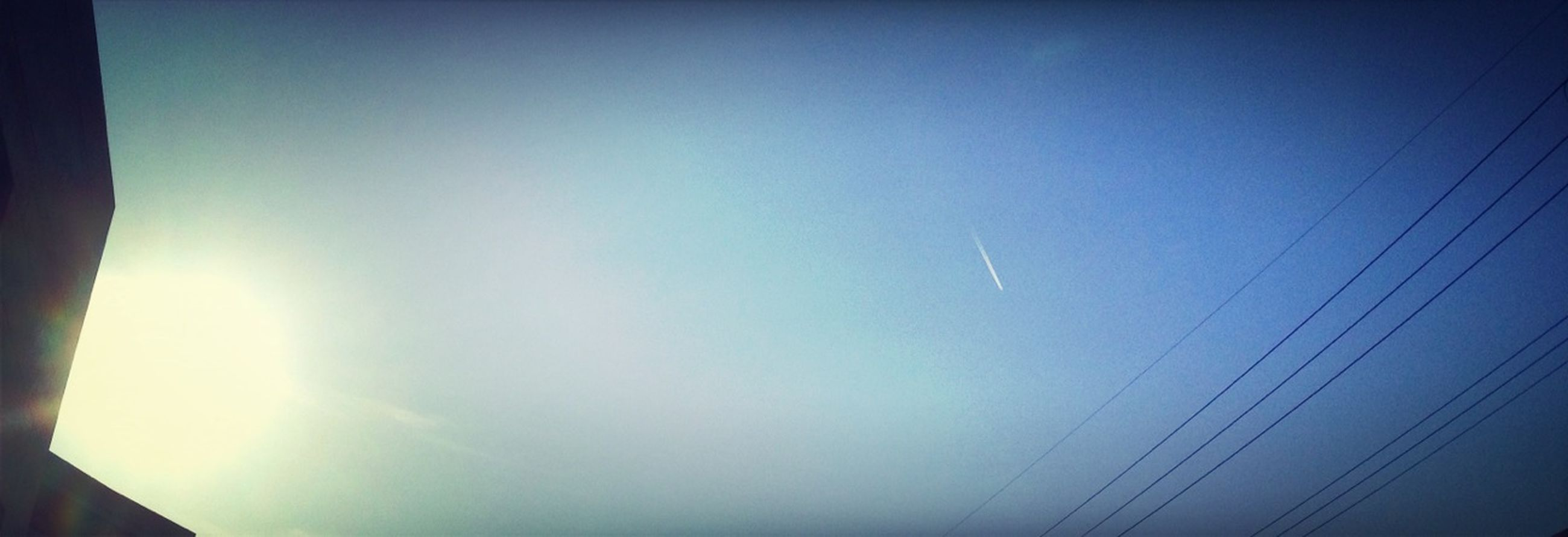 low angle view, sky, blue, silhouette, copy space, sun, clear sky, power line, electricity, vapor trail, cable, sunbeam, connection, nature, sunlight, beauty in nature, outdoors, no people, scenics, tranquility