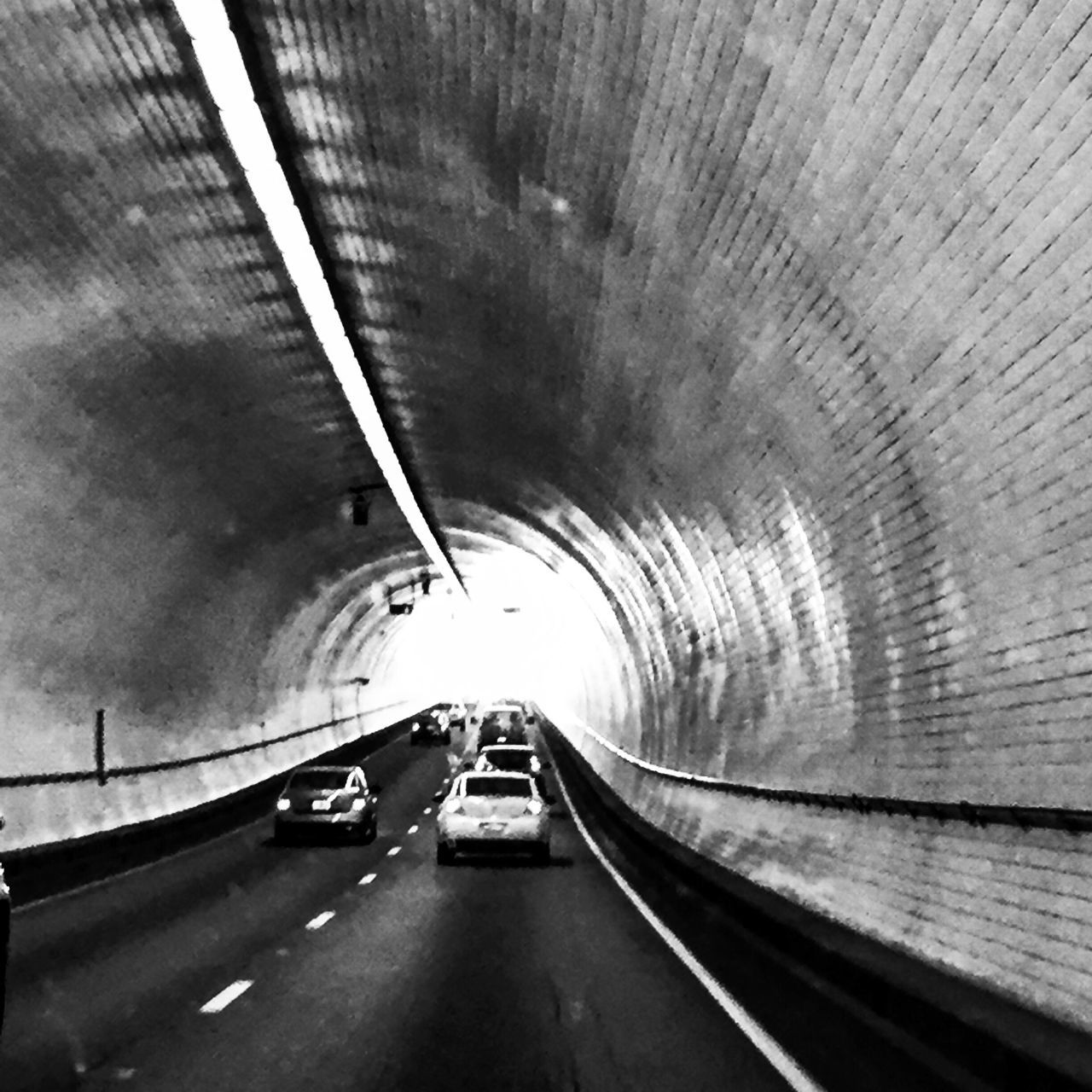 tunnel, transportation, road, the way forward, diminishing perspective, built structure, car, indoors, arch, land vehicle, light at the end of the tunnel, architecture, illuminated, mode of transport, bridge - man made structure, curve, day, no people, city, parking garage