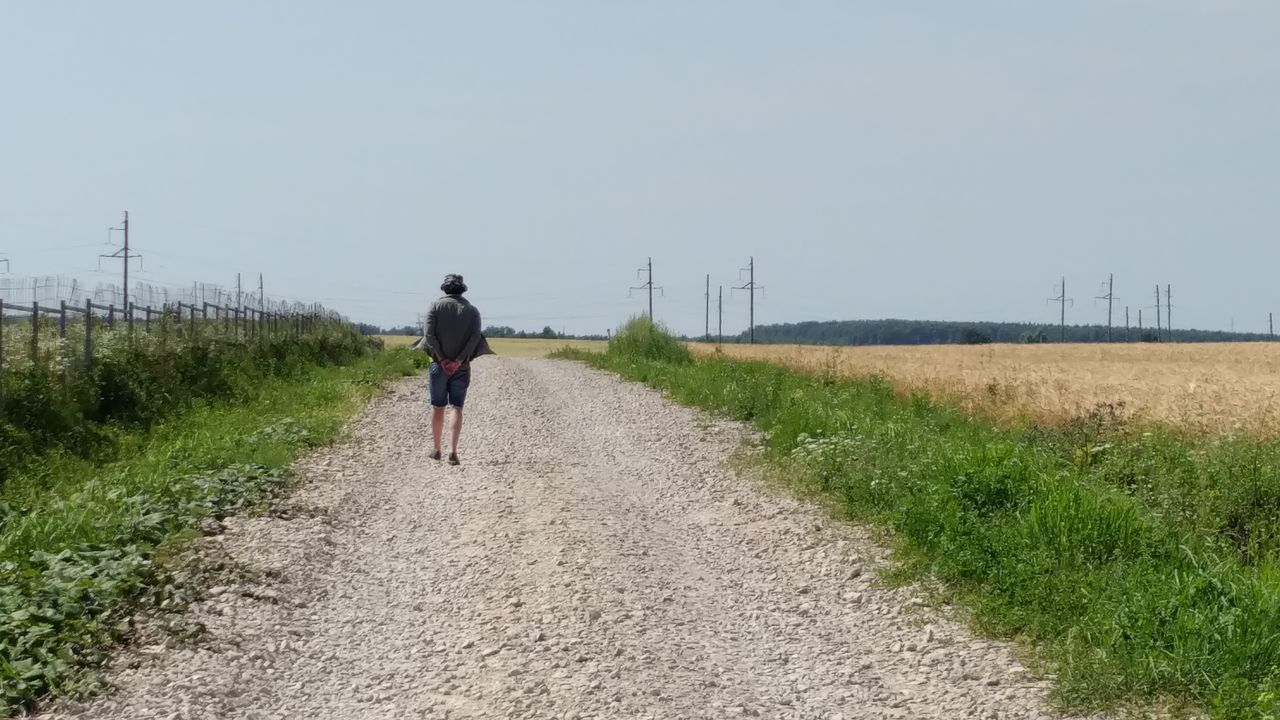walking, full length, rear view, real people, one person, day, the way forward, field, lifestyles, nature, road, men, leisure activity, transportation, adventure, outdoors, grass, bicycle, sky, clear sky, rural scene, young adult, people