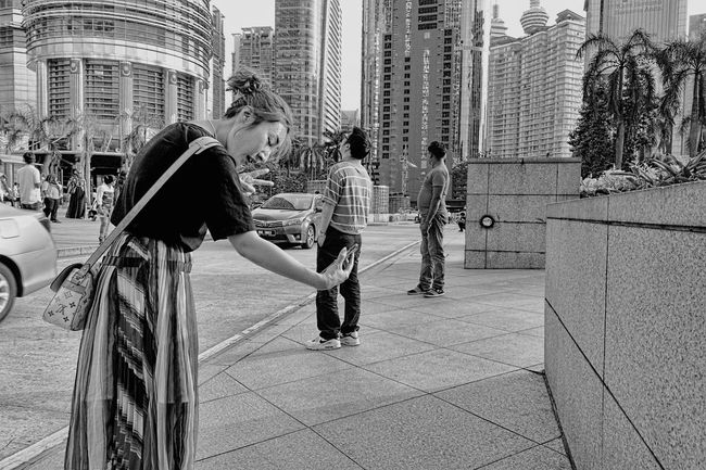 A tourist looks like a Kyrgyz or Kazakhs selfie in front KLCC Tower with the phone at one but #blacknwhite #kids #fotodroids #kloster #selfie #streetphotography Building Exterior City City Life City Street Leisure Activity Lifestyles Streetphoto_bw First Eyeem Photo