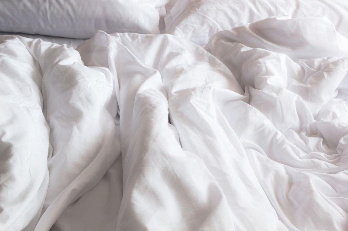 top view of white pillow on bed and with wrinkle messy blanket in bedroom, from sleeping in a long night. Bed Bedroom Close-up Crumpled Indoors  Luxury Messy Pillow Sheet White Color Winkle Wrinkled