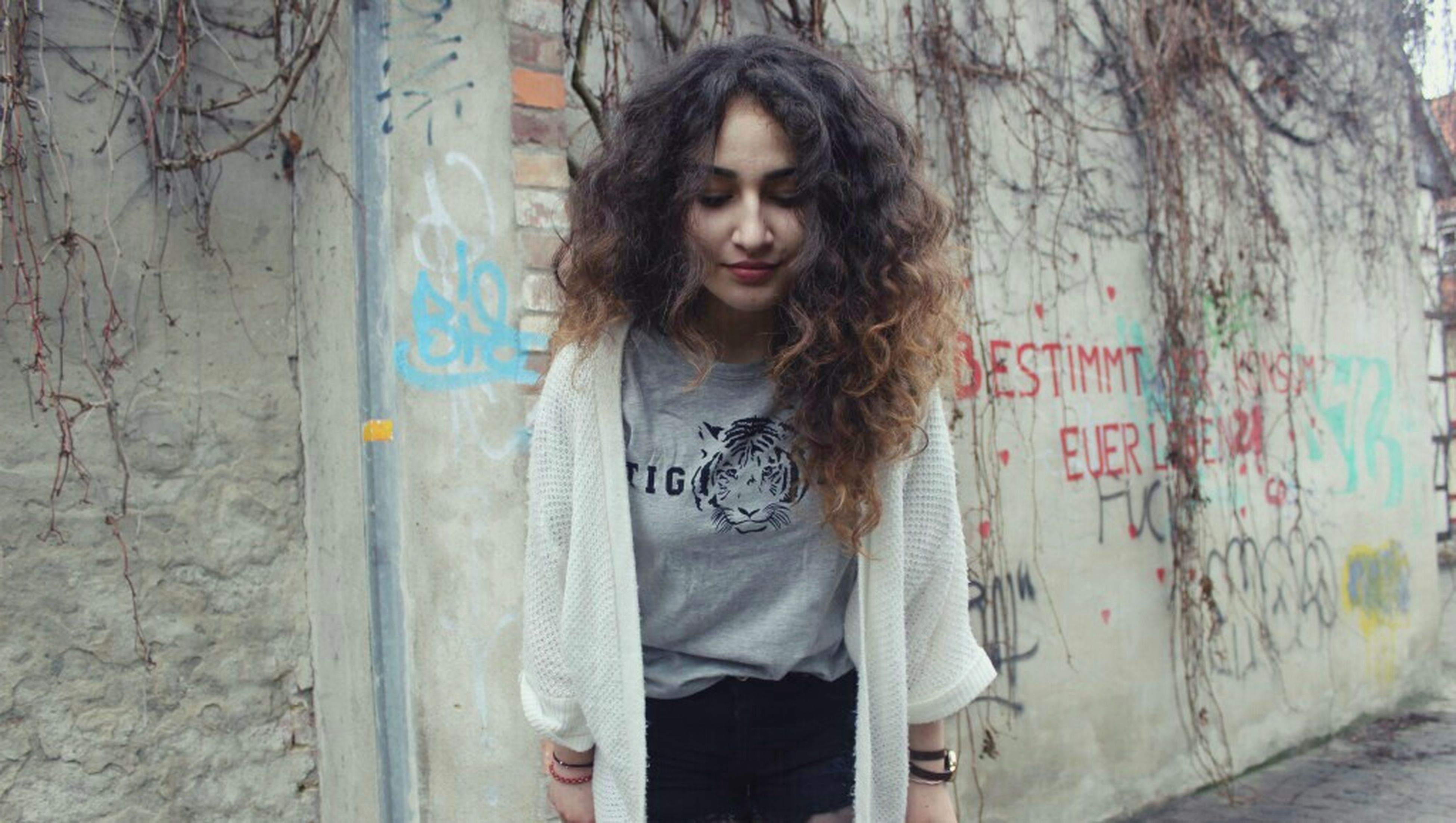 young adult, young women, person, front view, long hair, wall - building feature, looking at camera, casual clothing, portrait, lifestyles, standing, graffiti, built structure, waist up, architecture, three quarter length, wall
