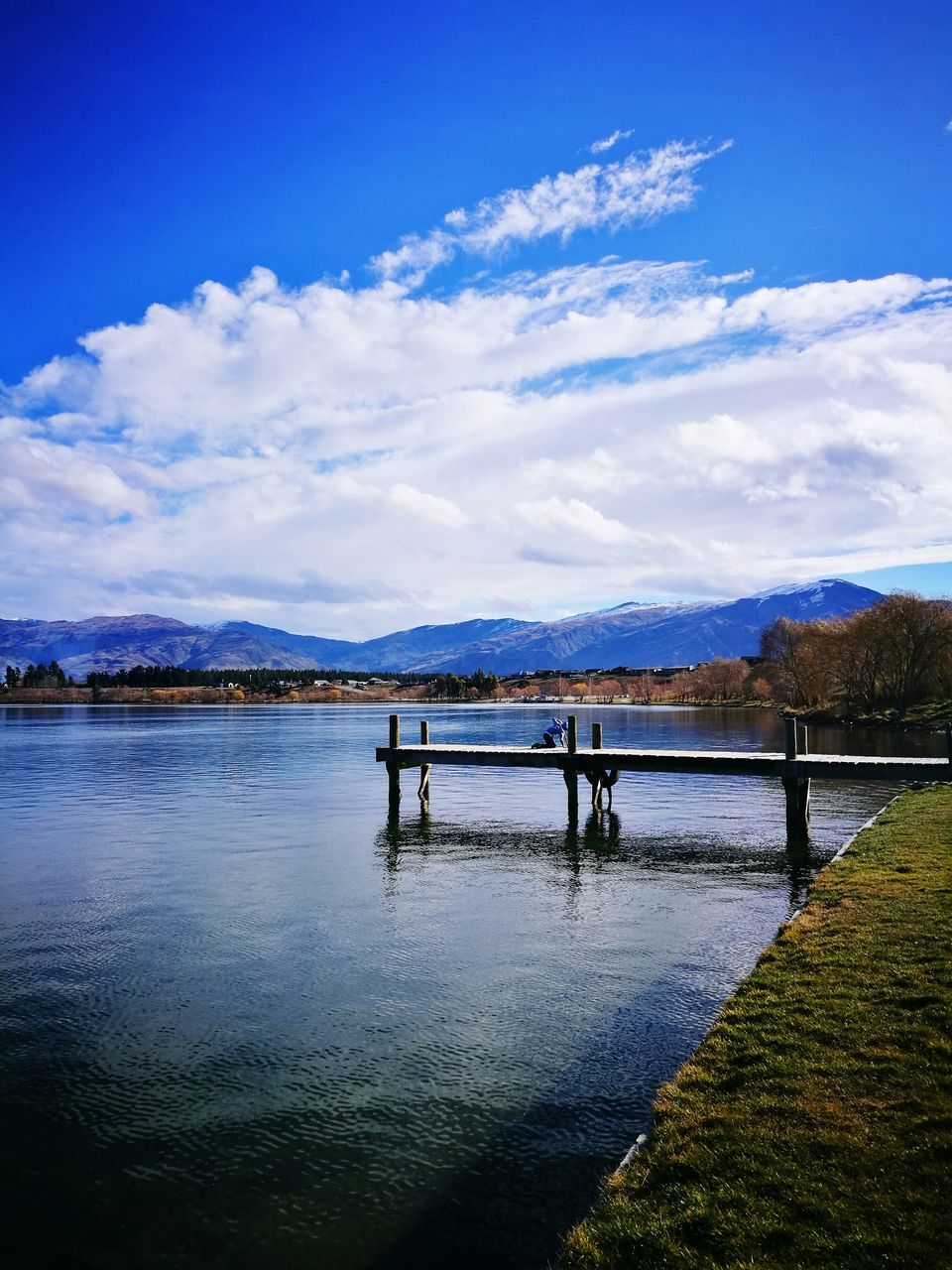 water, sky, cloud - sky, river, scenics, blue, mountain, nature, tranquility, tranquil scene, beauty in nature, outdoors, day, mountain range, bridge - man made structure, no people, architecture, tree