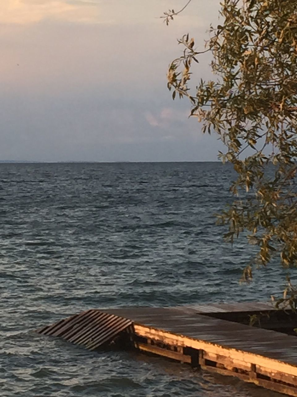 sea, water, horizon over water, tranquil scene, sunset, scenics, no people, beauty in nature, nature, wood - material, tranquility, outdoors, beach, sky, day