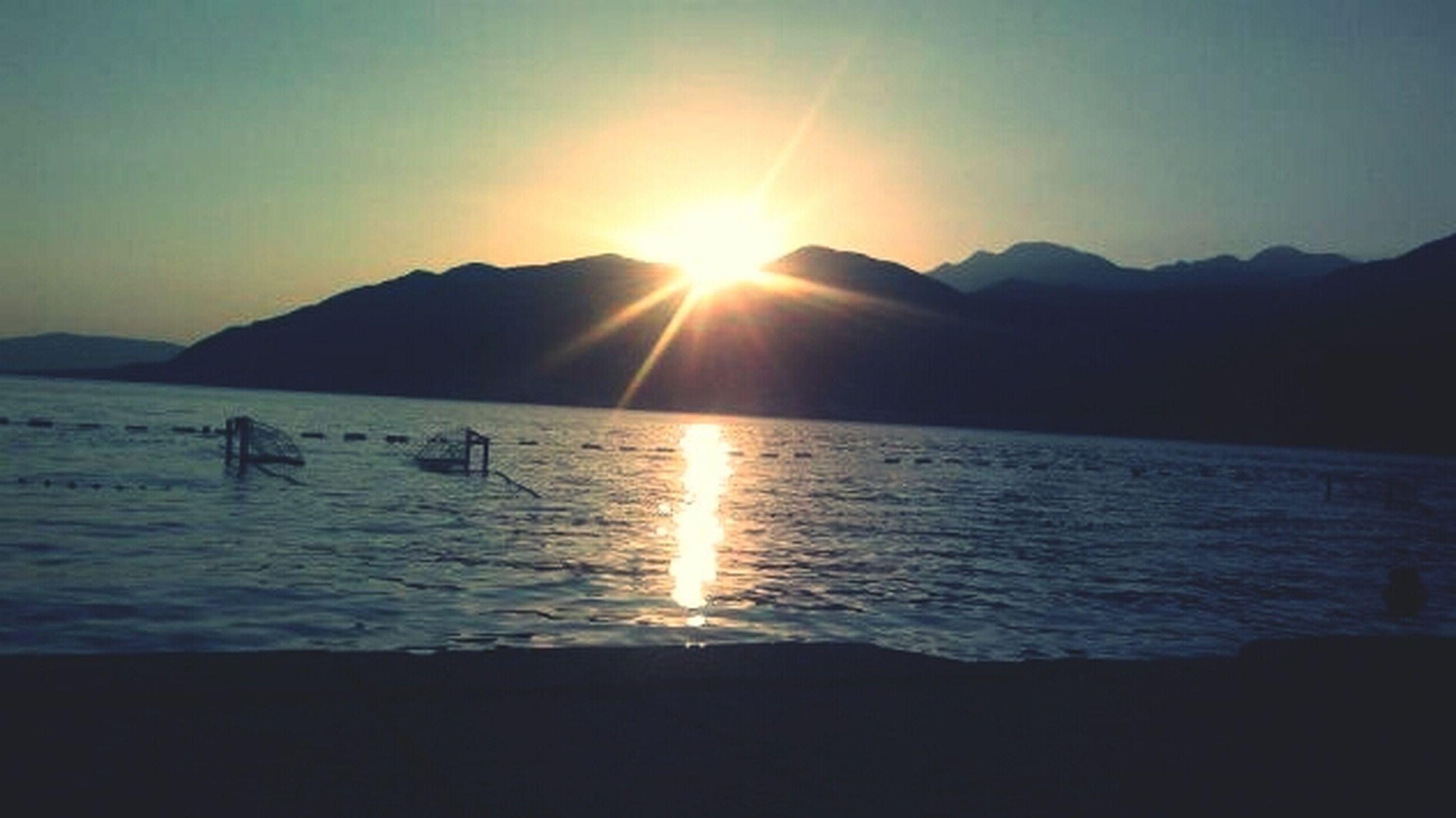 water, sun, mountain, scenics, tranquil scene, sunset, sea, tranquility, beauty in nature, sunlight, reflection, silhouette, sunbeam, mountain range, nature, lens flare, idyllic, sky, clear sky, lake