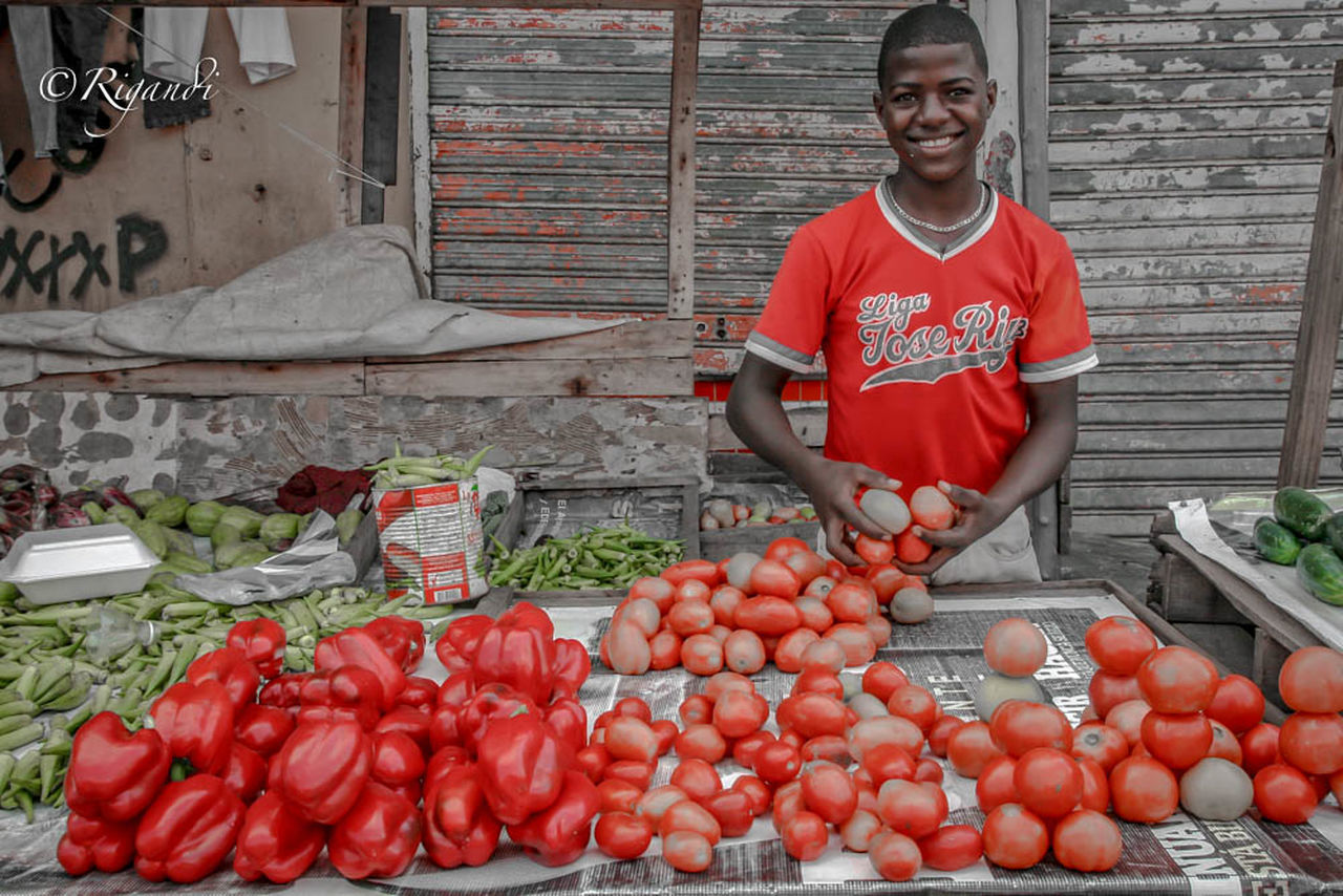red Abundance Business Choice Day Food Food And Drink Freshness Front View Fruit Healthy Eating Large Group Of Objects Looking At Camera Market Market Stall Men One Person Outdoors Portrait Real People Red Retail  Smiling Standing Tomato Vegetable