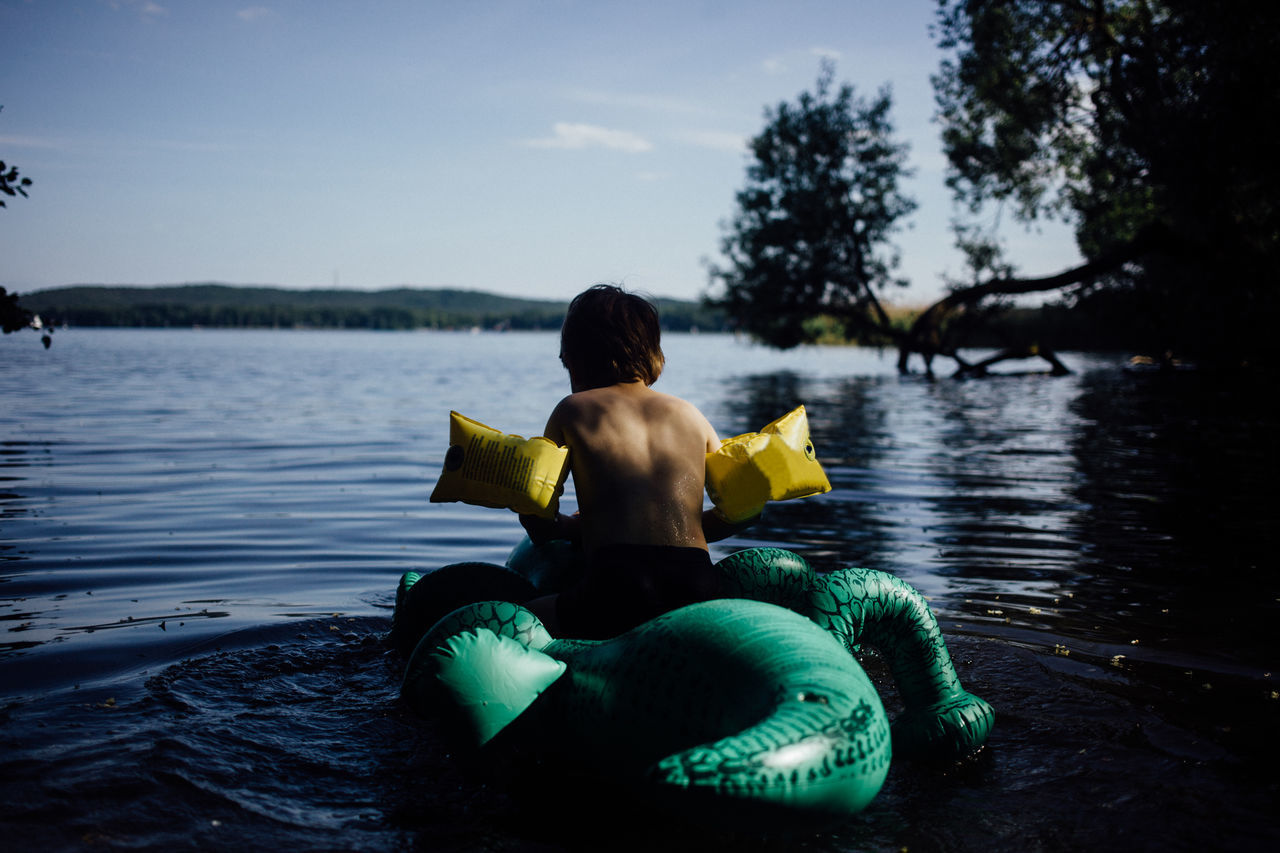 beauty in Nature childhood day lake leisure activity Nature one person outdoors people real people Rear view Sitting sky Tree water women