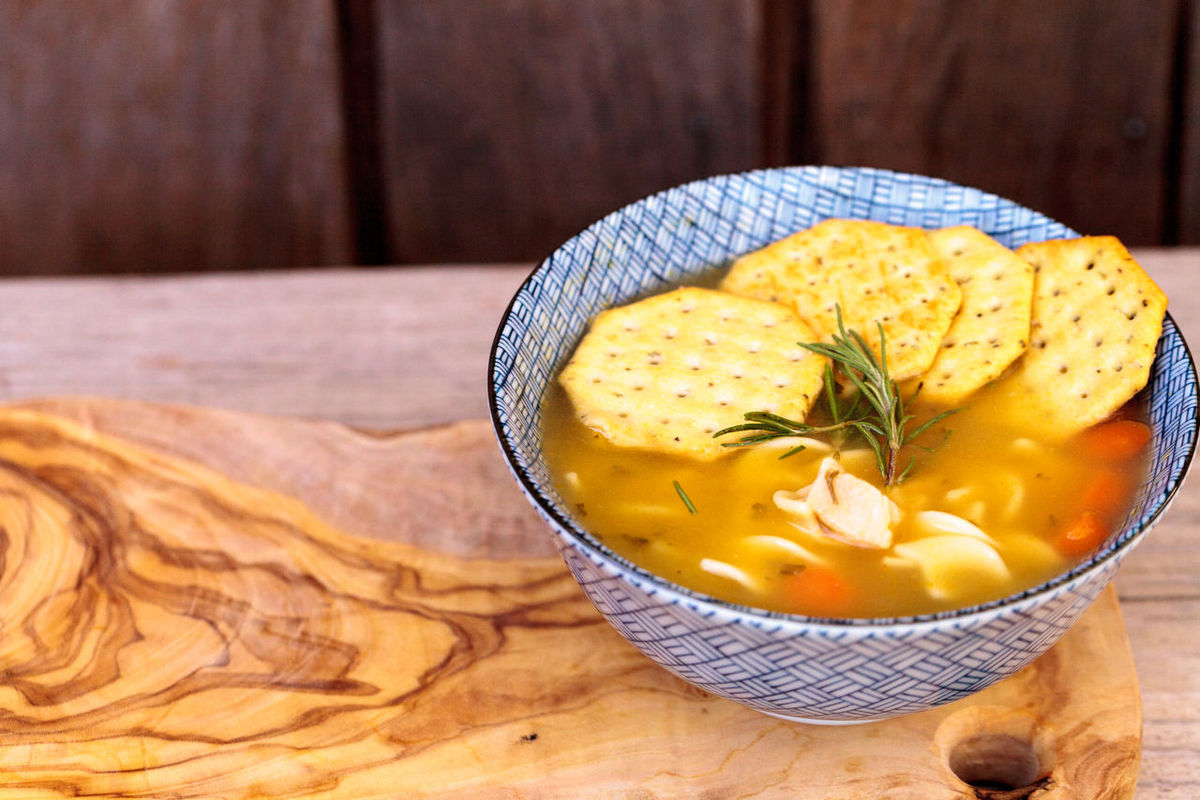 Chicken noodle soup in a blue and white bowl with crackers, all sitting on a wood cutting board. Bowl Broth Chicken Noodle Soup Chicken Soup Comfort Food Crackers Food Health Home Remedies Lunch Sick Soup