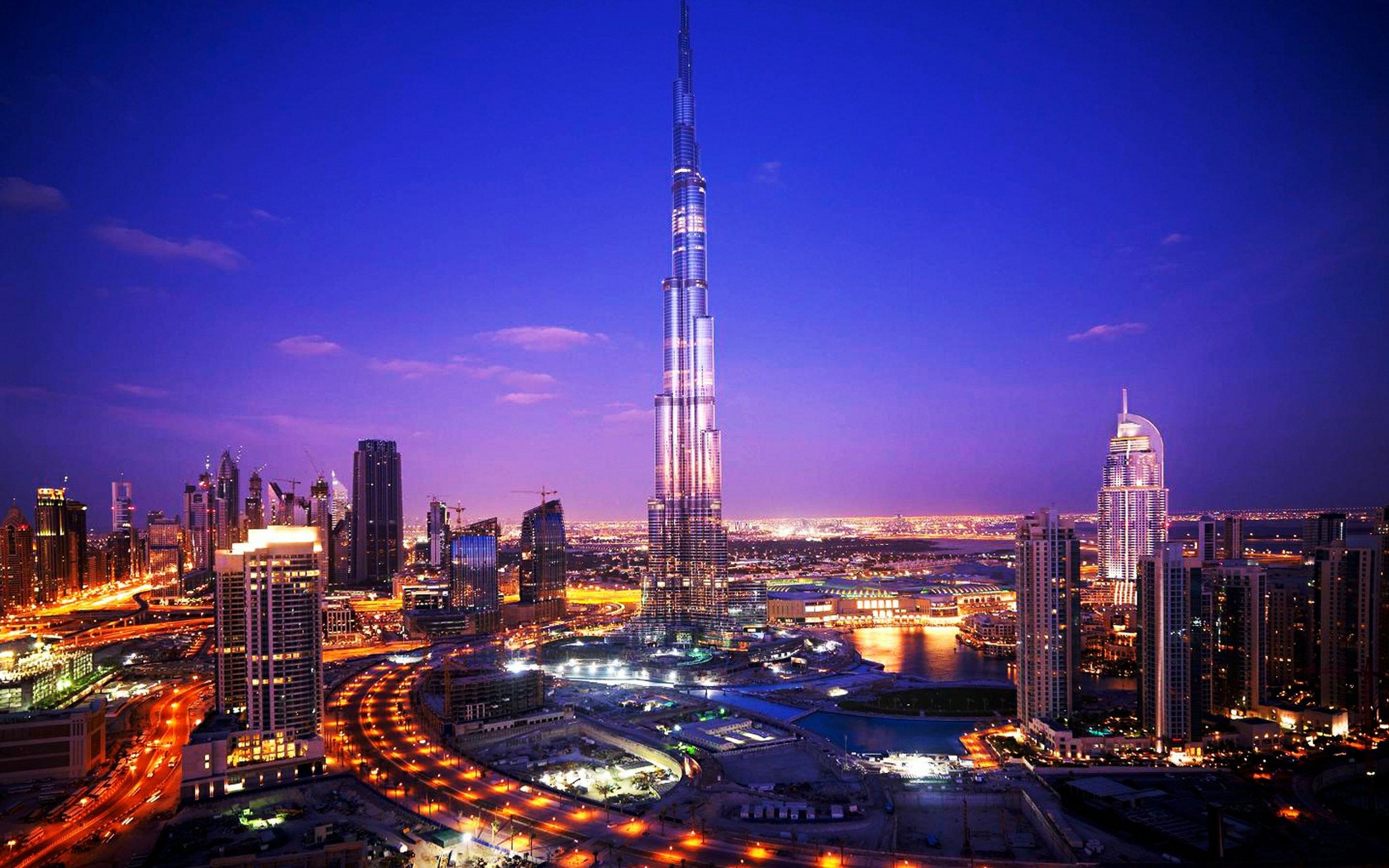 illuminated, city, architecture, building exterior, cityscape, built structure, night, tall - high, tower, skyscraper, capital cities, sky, city life, travel destinations, high angle view, modern, blue, transportation, travel, dusk