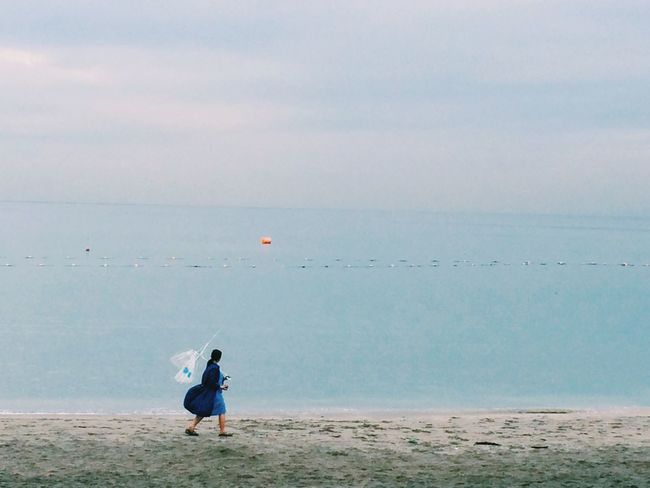 a girl with broken umbrella On The Beach In The Rain Edge Of The World