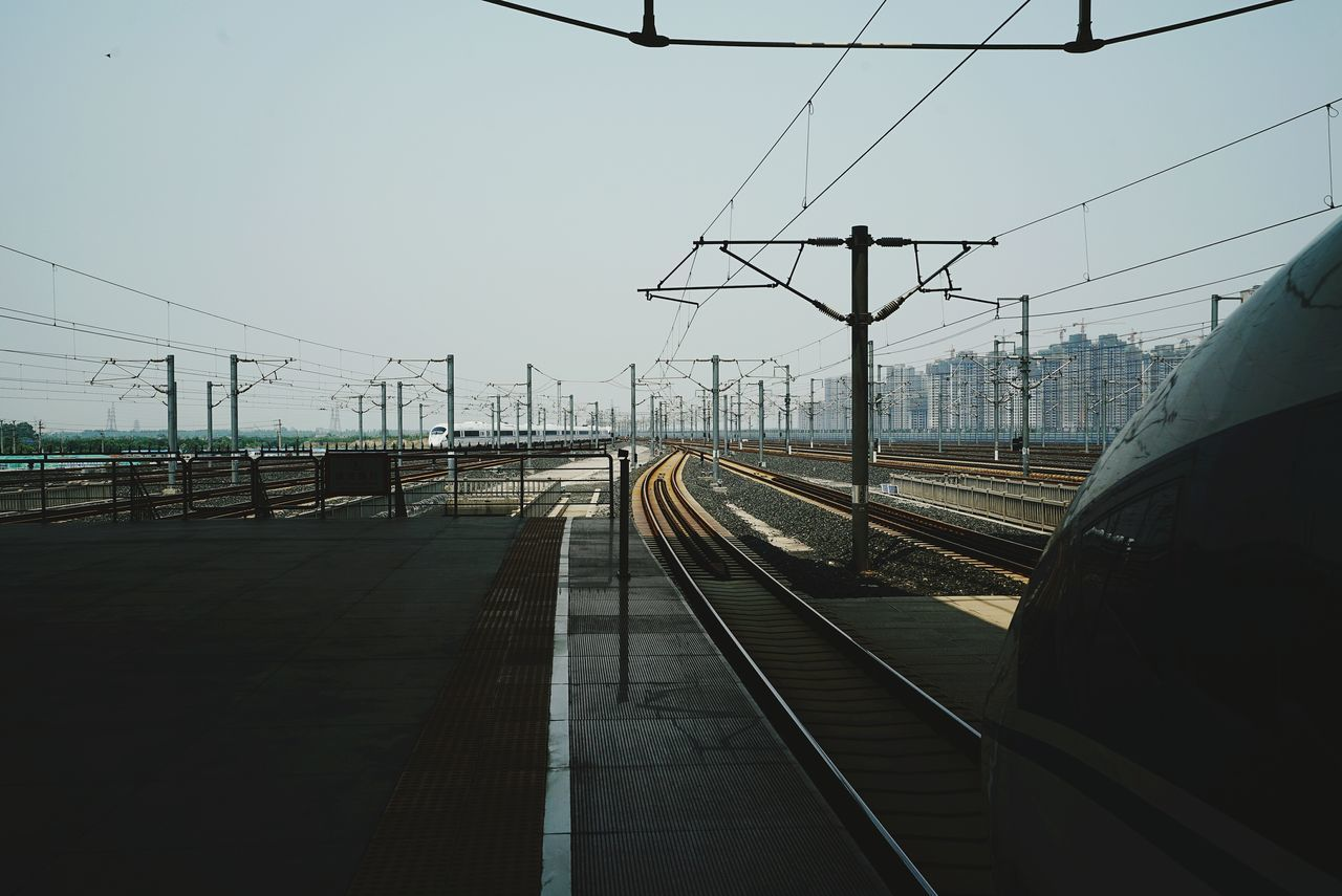 Electricity Pylons Amidst Railroad Tracks Against Sky Seen From Station Platform