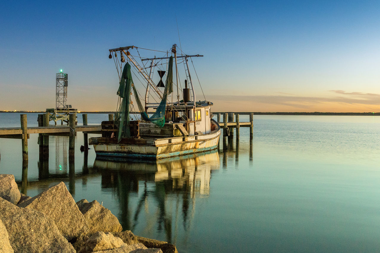 A shrimp boat moored along the Texas City Beauty In Nature Blue Boat Calm Day Harbor Idyllic Mast Mode Of Transport Nature Nautical Vessel No People Ocean Outdoors Reflection Sailboat Scenics Sky Standing Water Tranquil Scene Tranquility Water