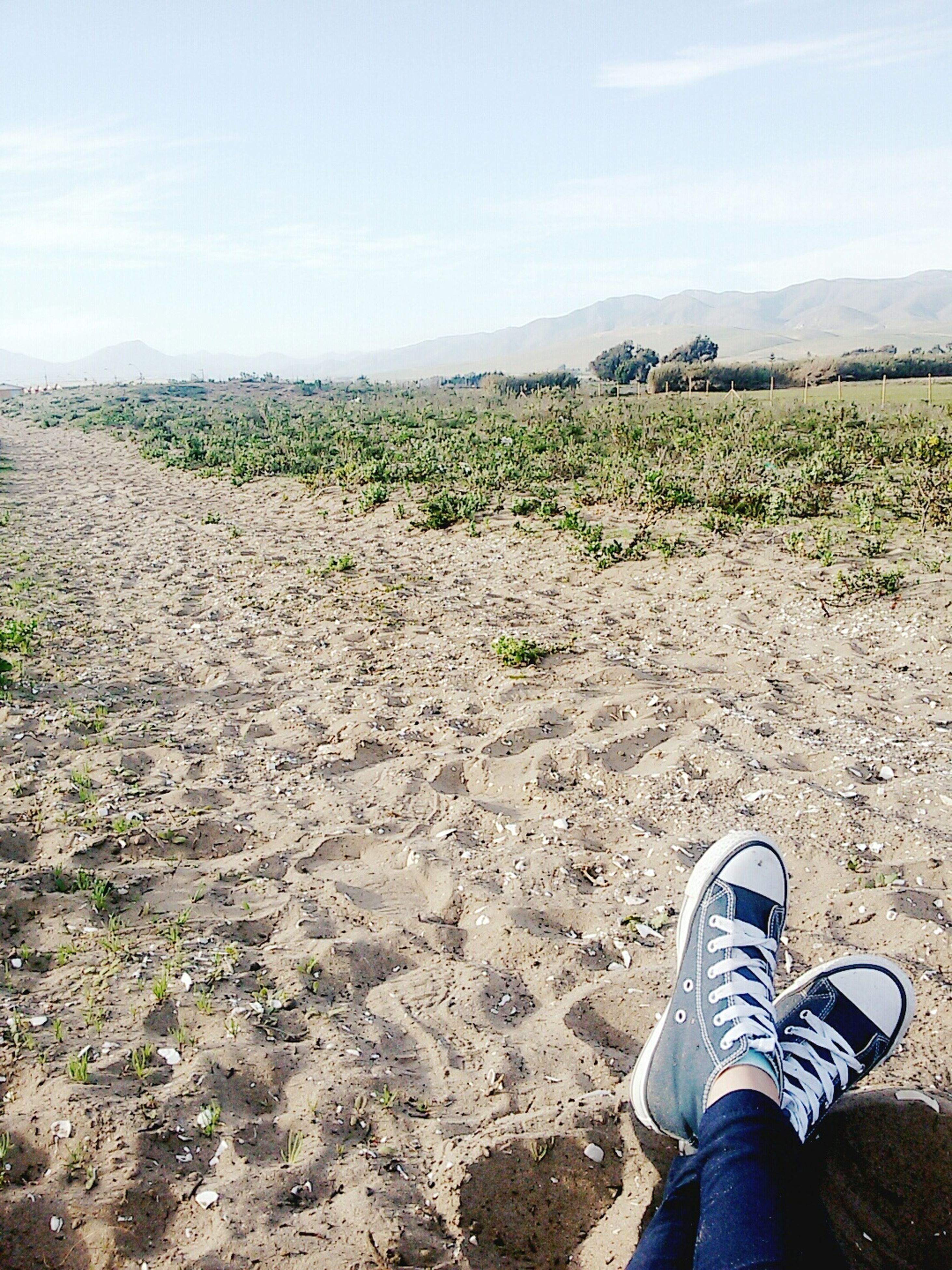 low section, person, shoe, personal perspective, sky, landscape, mountain, field, lifestyles, standing, leisure activity, unrecognizable person, men, tranquility, nature, footwear, grass